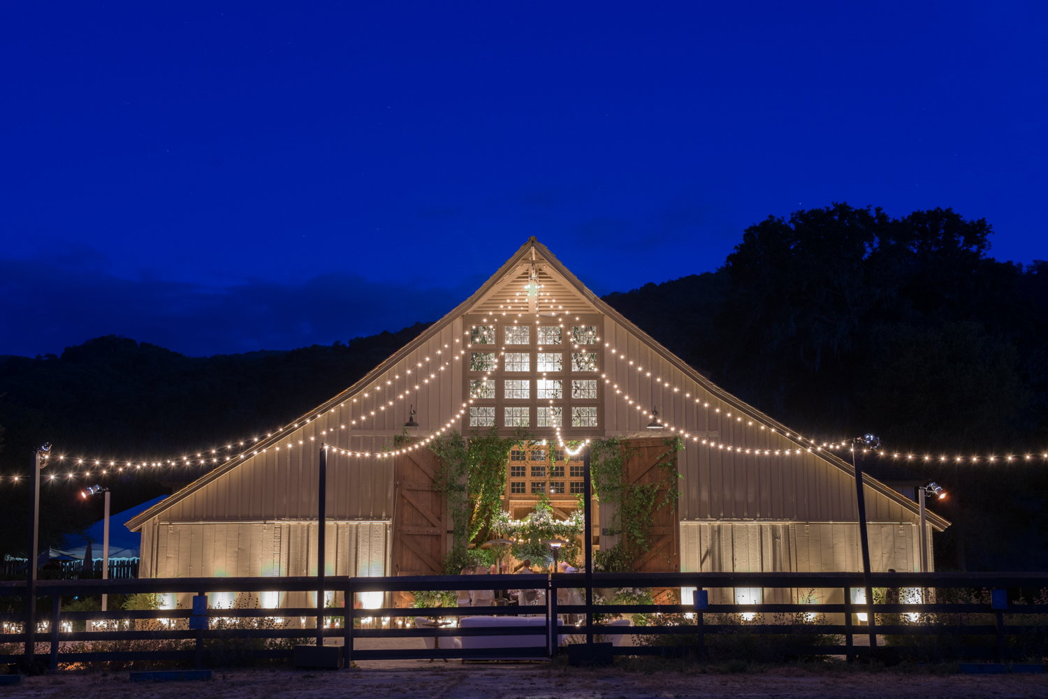 The indoor reception continues as dusk falls over the steep-roofed barn strung with lights and covered over with ivy; photo by Sylvie Gil