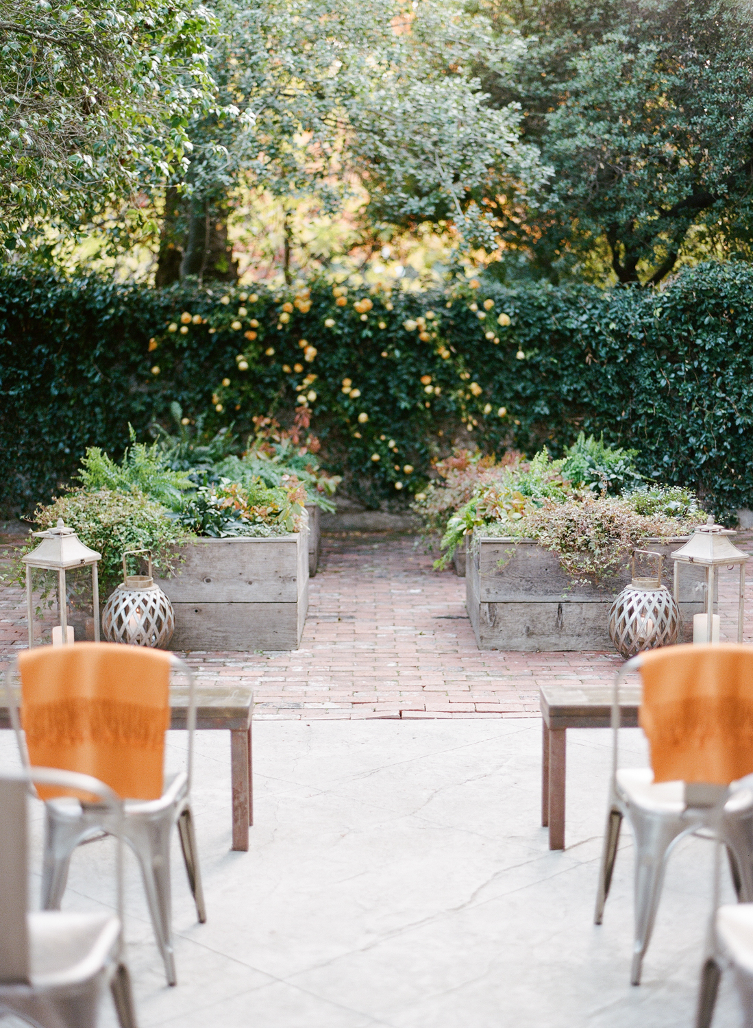 Steel industrial accents mixed with wood, orange shawls for guests; Sylvie Gil Photography