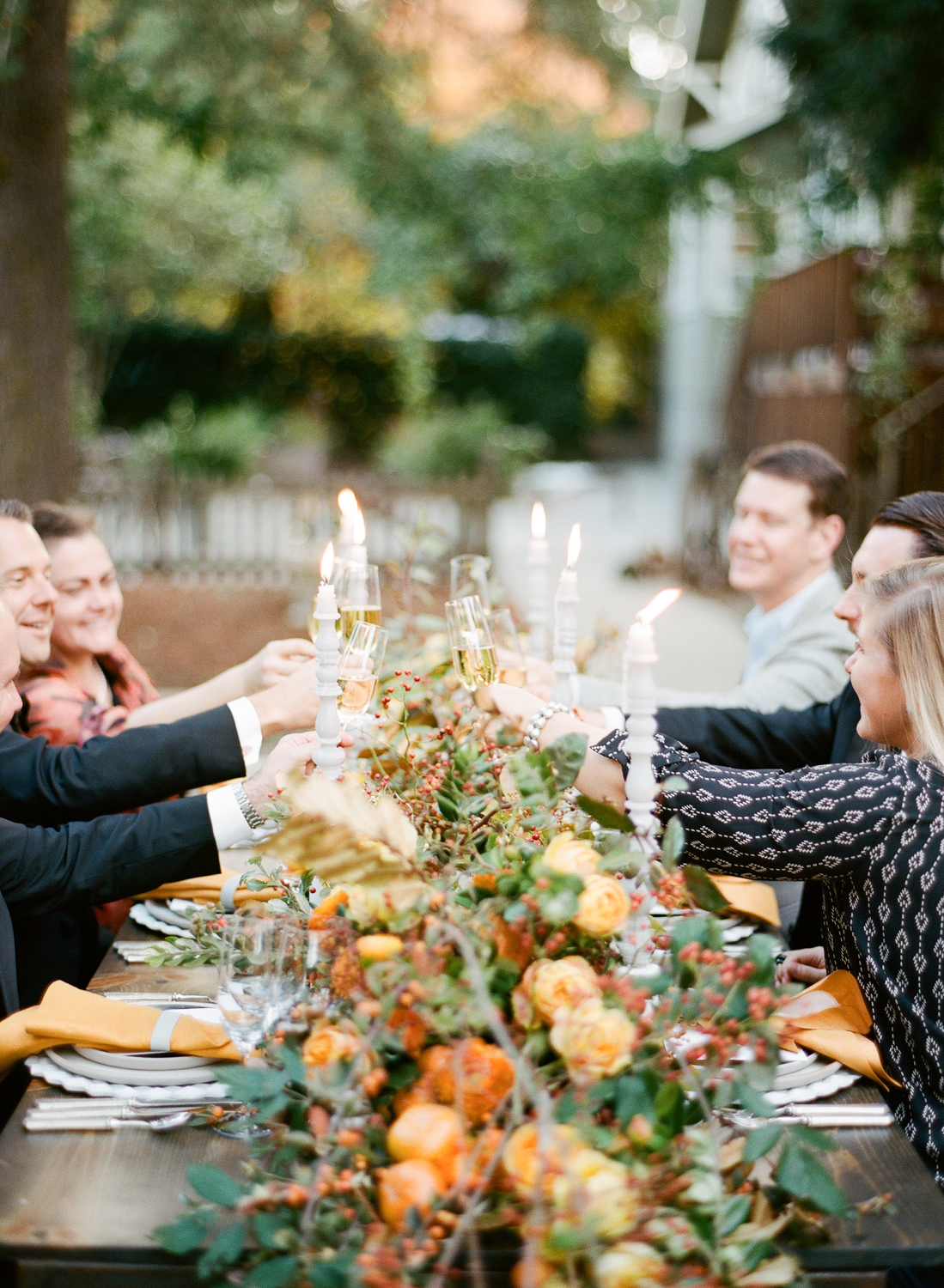 Guests toast champagne over a stunning wild rosehip, persimmon, and peony table garland centerpiece; Sylvie Gil Photography
