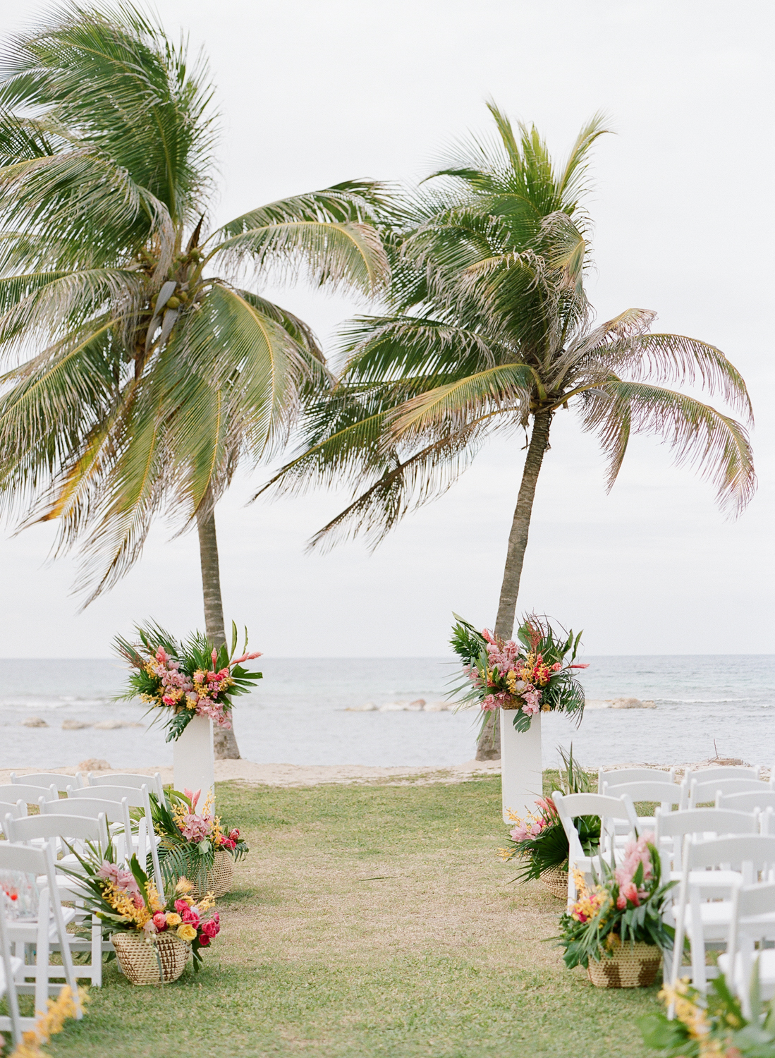 Local tropical florals line the aisle of the beachside wedding ceremony; Sylvie Gil Photography