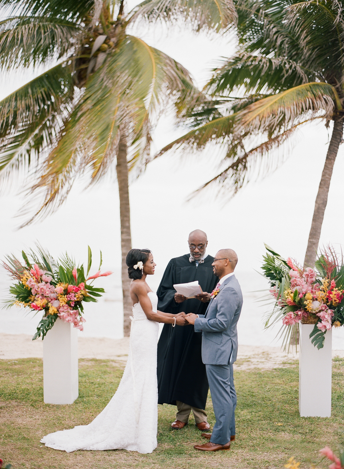 Bride and groom at Montego Bay, Jamaica ceremony, exchanging vows underneath palm trees; Sylvie Gil Photography