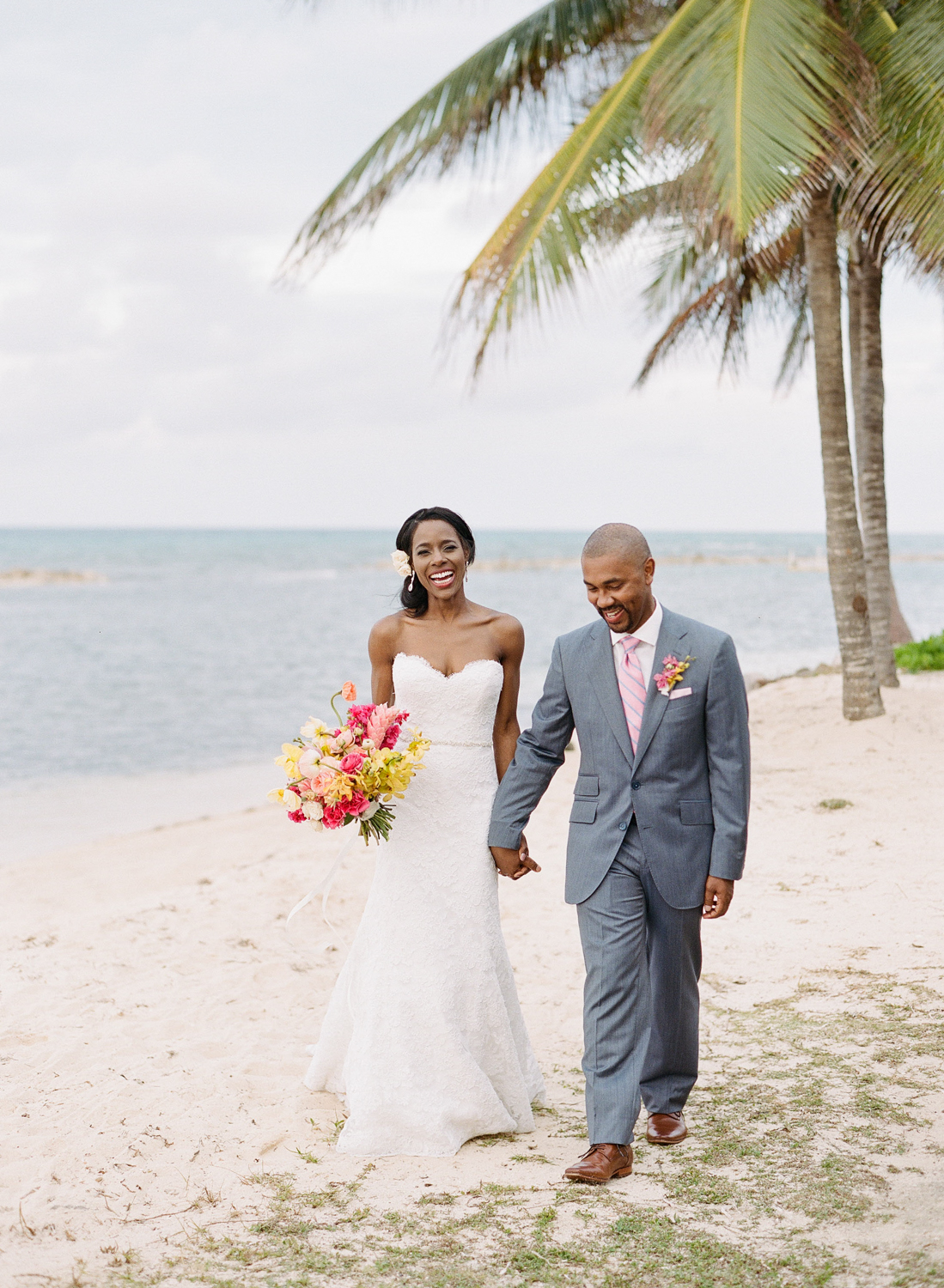 Couple in love walks white sand beach in Montego Bay, Jamaica after wedding ceremony; Sylvie Gil Photography