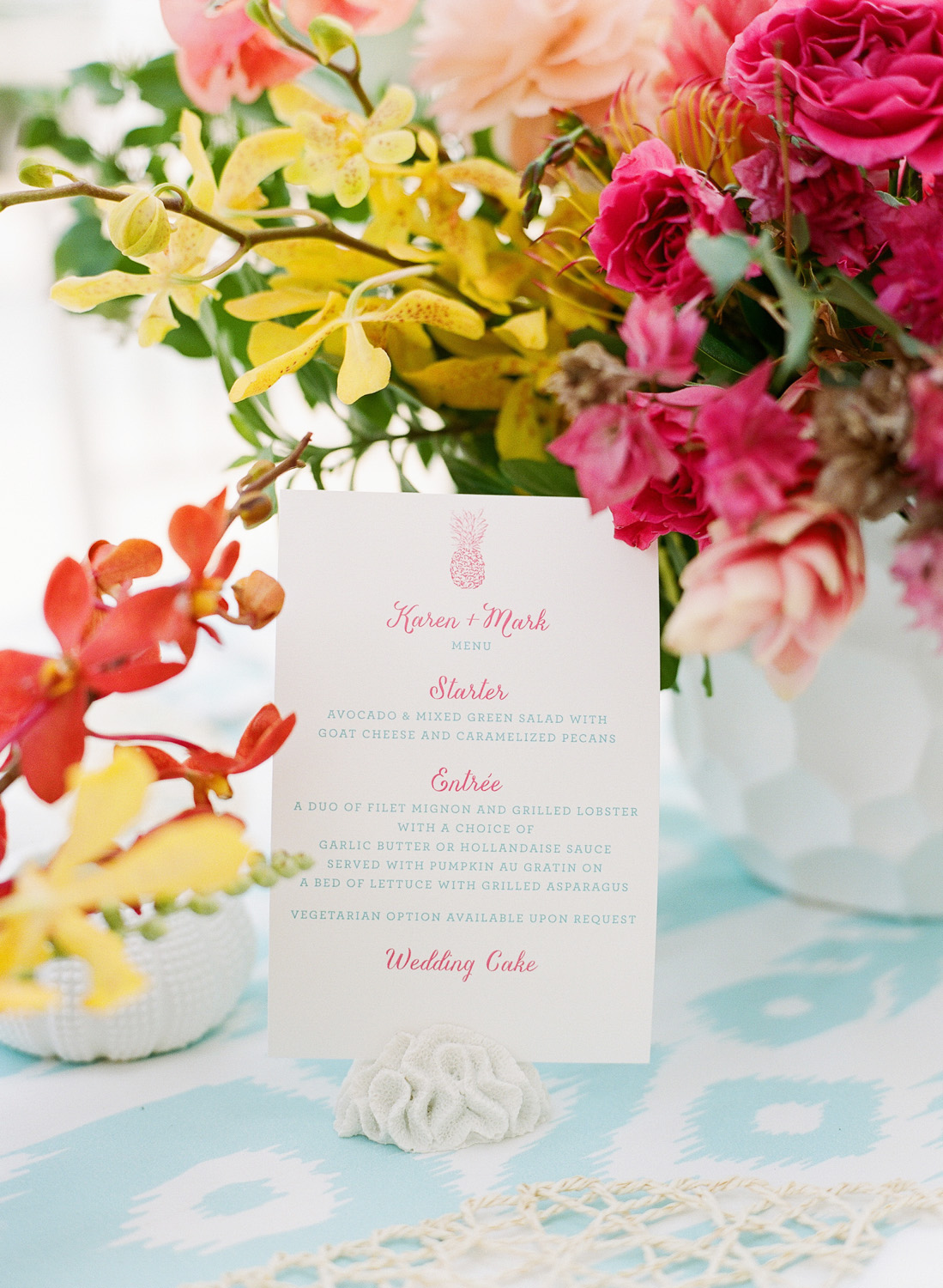 Pineapple motif menu held with coral paperweight at reception tables; Sylvie Gil Photography