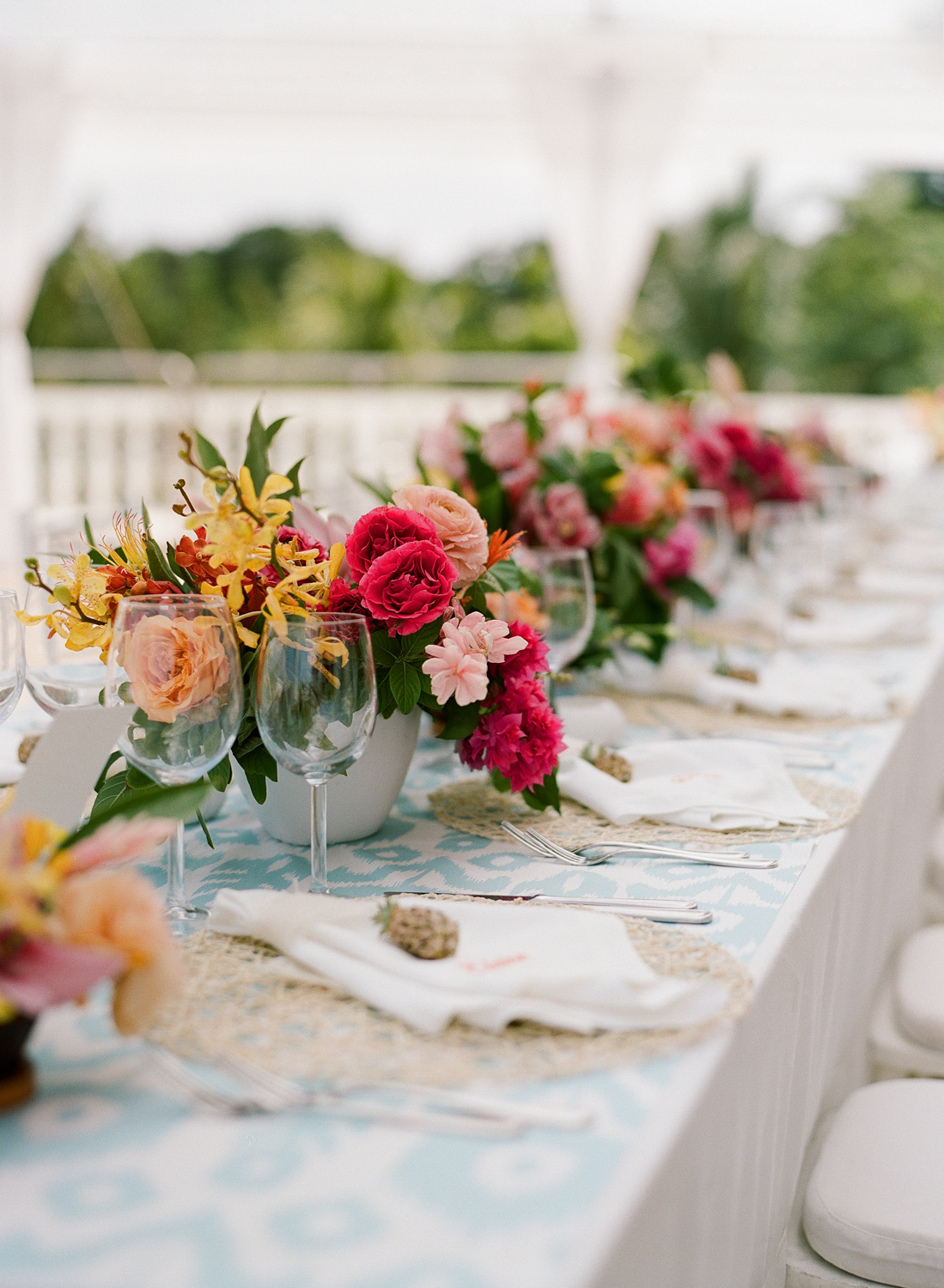 Pineapple accents, wicker placemats, ikat tablecloth, tropical bloom centerpieces; Sylvie Gil Photography