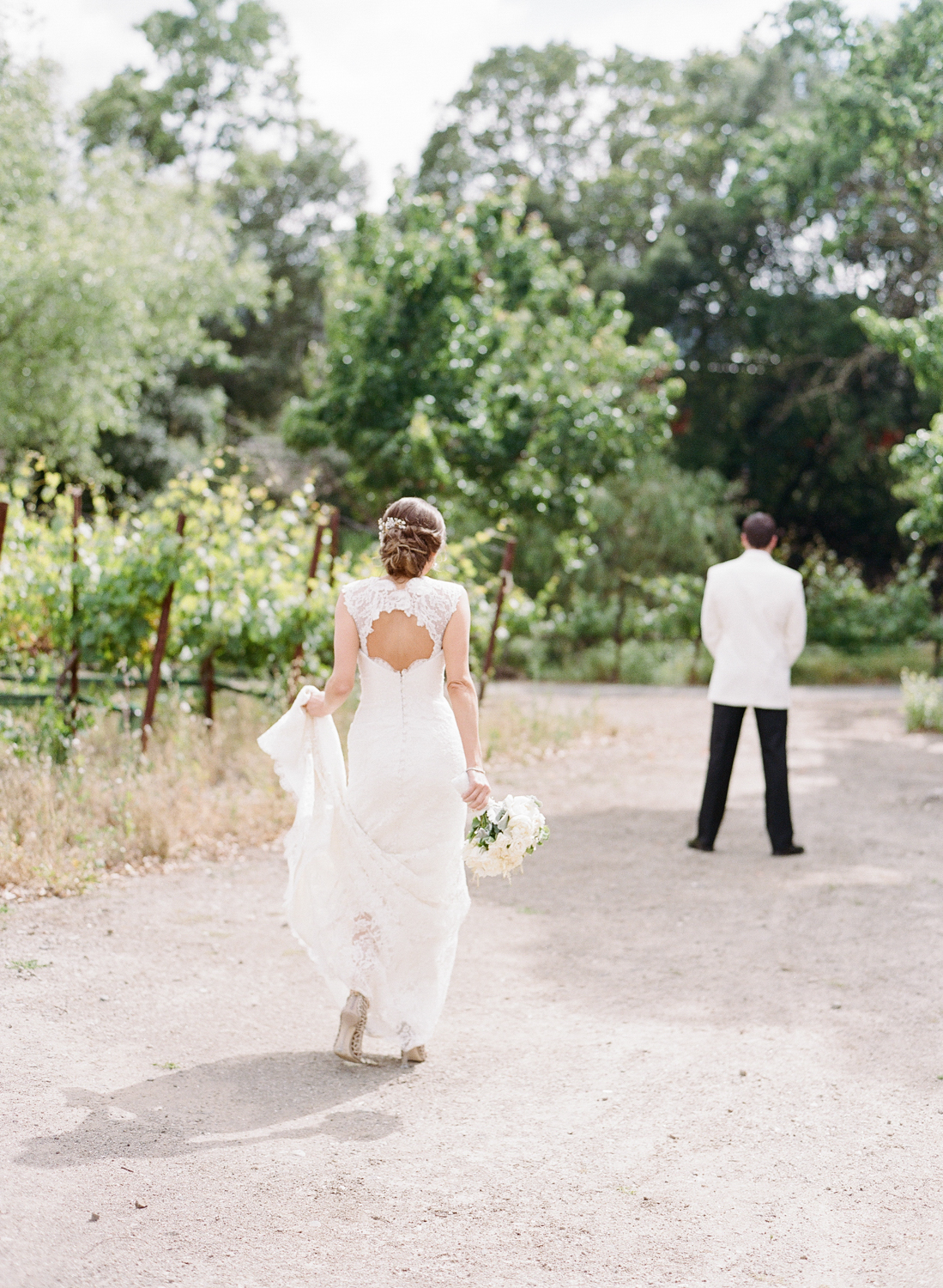 Bride walking up to the groom for the first look in Yountville vineyards outside Vintage Estates; Sylvie Gil Photography