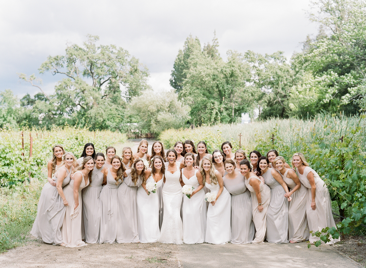 Bride with her 27 bridesmaids in white, grey, beige Monique Lhuillier gowns; Sylvie Gil Photography