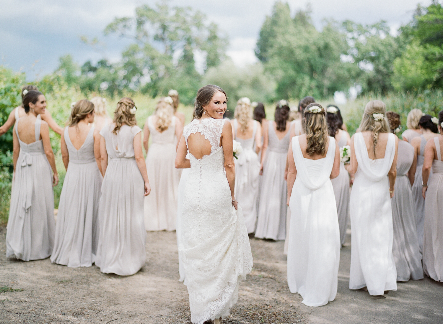 Bride in backless lace Anna Maier gown with 27 bridesmaids in neutral Monique Lhuillier gowns; Sylvie Gil Photography