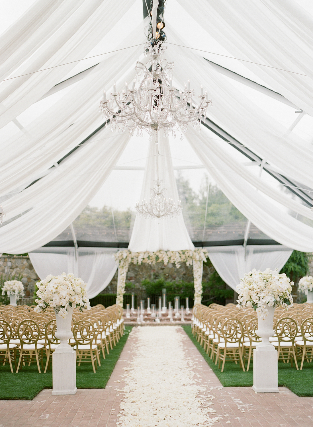 Crystal chandeliers hang from the awning draped tent ceremony space decorated with white florals; Sylvie Gil Photography