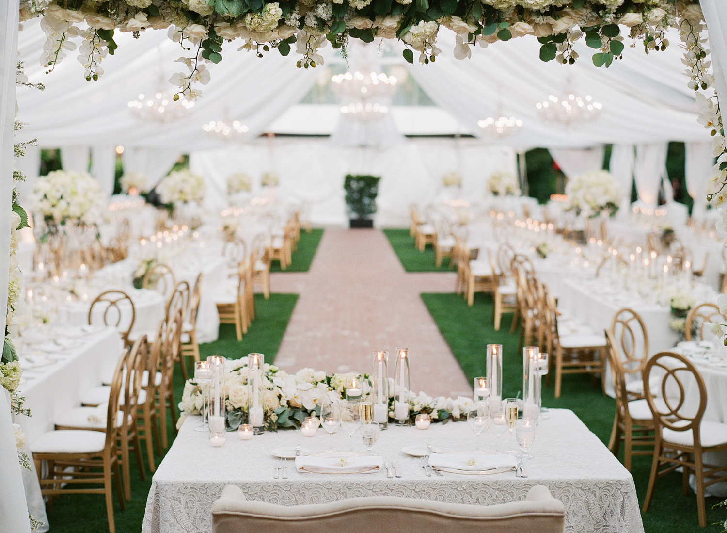 Head table for bride and groom framed by white floral garlands; Sylvie Gil Photography