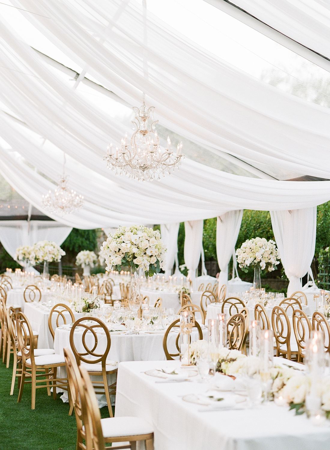 Dreamy white linens draped from the ceiling of the tent with crystal chandeliers over gold and white reception tables; Sylvie Gil Photography