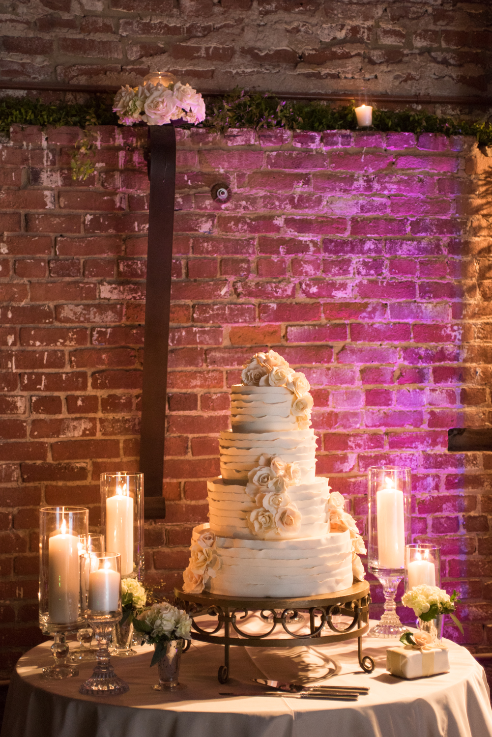 Four tier couple's cake, white ribbons decorated with buttercream roses made by Susan Morgan; Sylvie Gil Photography