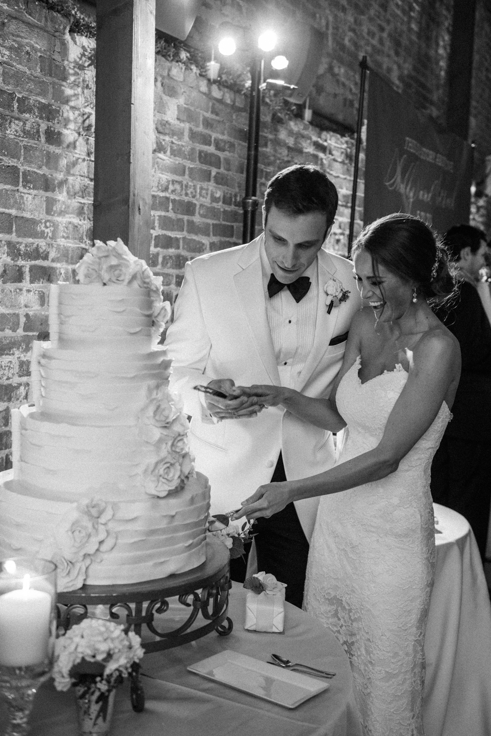 Bride and groom cutting the cake together at the pavilion reception at Vintage Estates; Sylvie Gil Photography