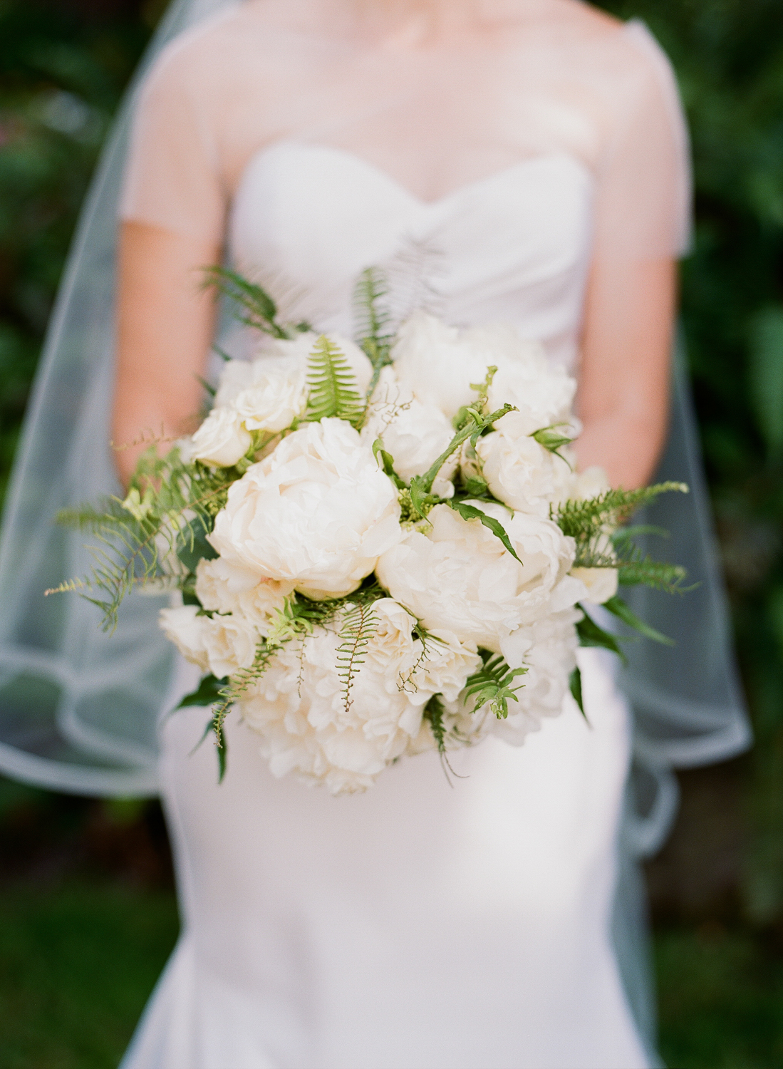 Bride in a contemporary Vera Wang wedding gown holds a white peony and fern bouquet; Sylvie Gil Photography