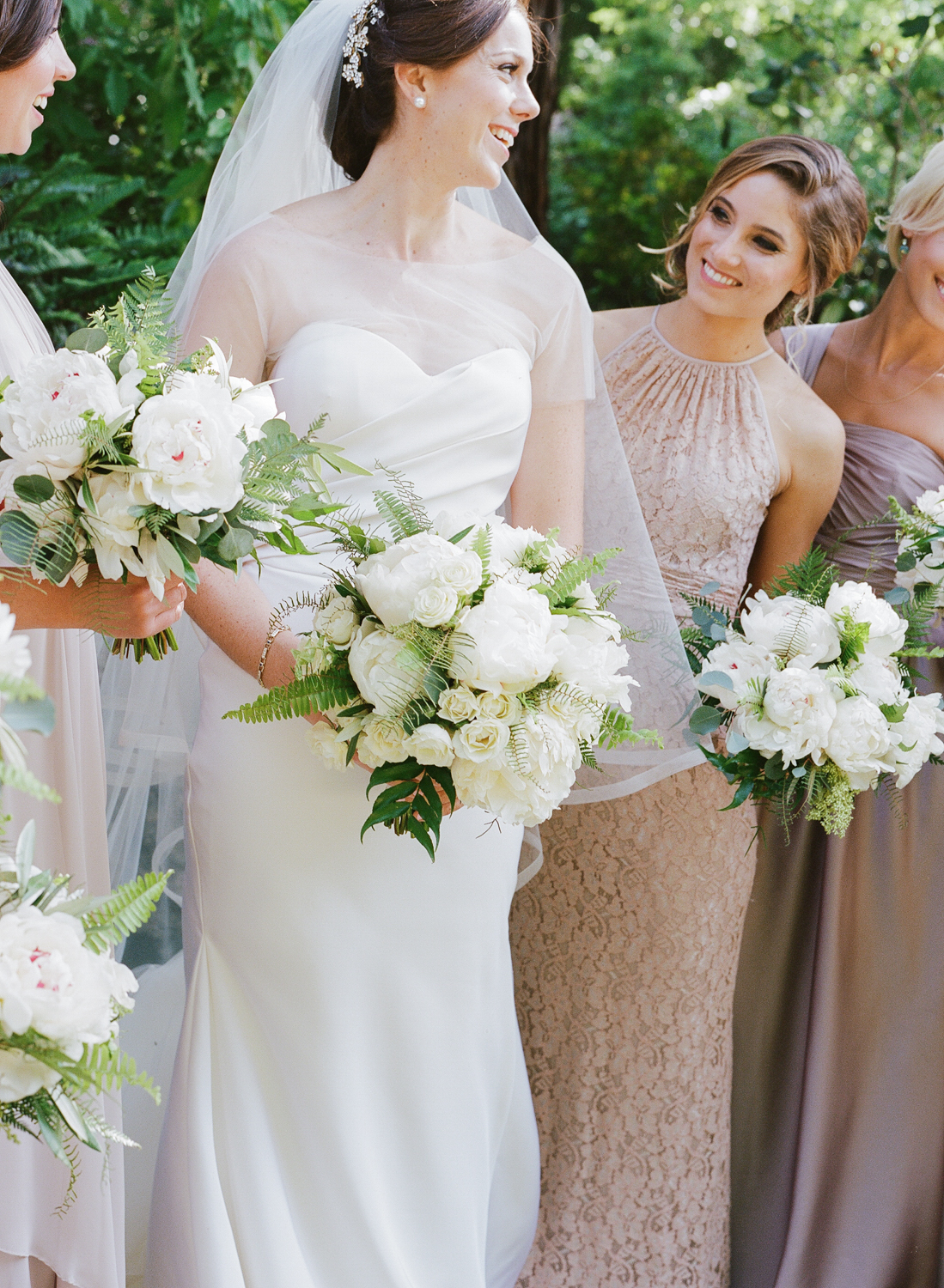 Bride and bridesmaids with white rose, peony, and fern bouquets; Sylvie Gill Photography