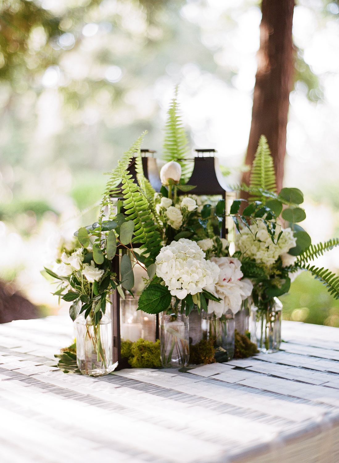 Lanterns decorated with moss and bottles of hydrangeas and ferns at the placecard table; Sylvie Gil Photography