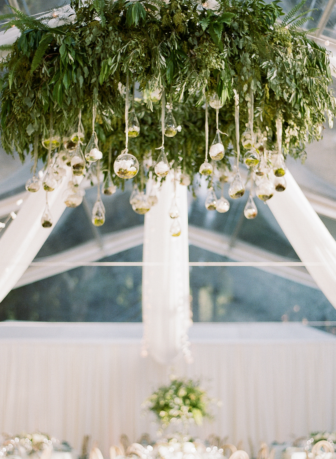 Tiny glass terrariums hang from a leafy wreath at the center of the clear paneled reception tent; Sylvie Gil Photography