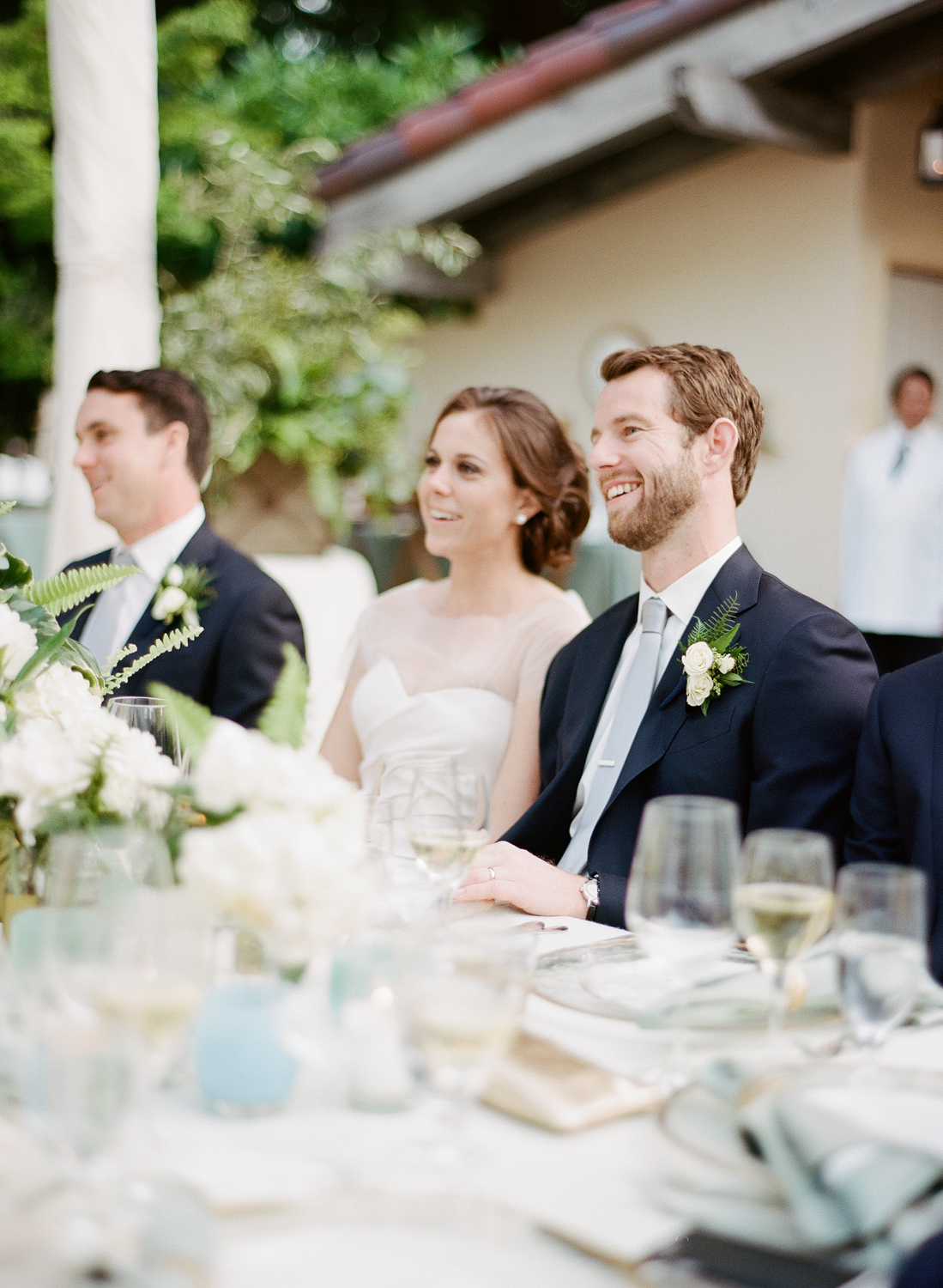 Bride and groom smile during reception toasts; Sylvie Gil Photography