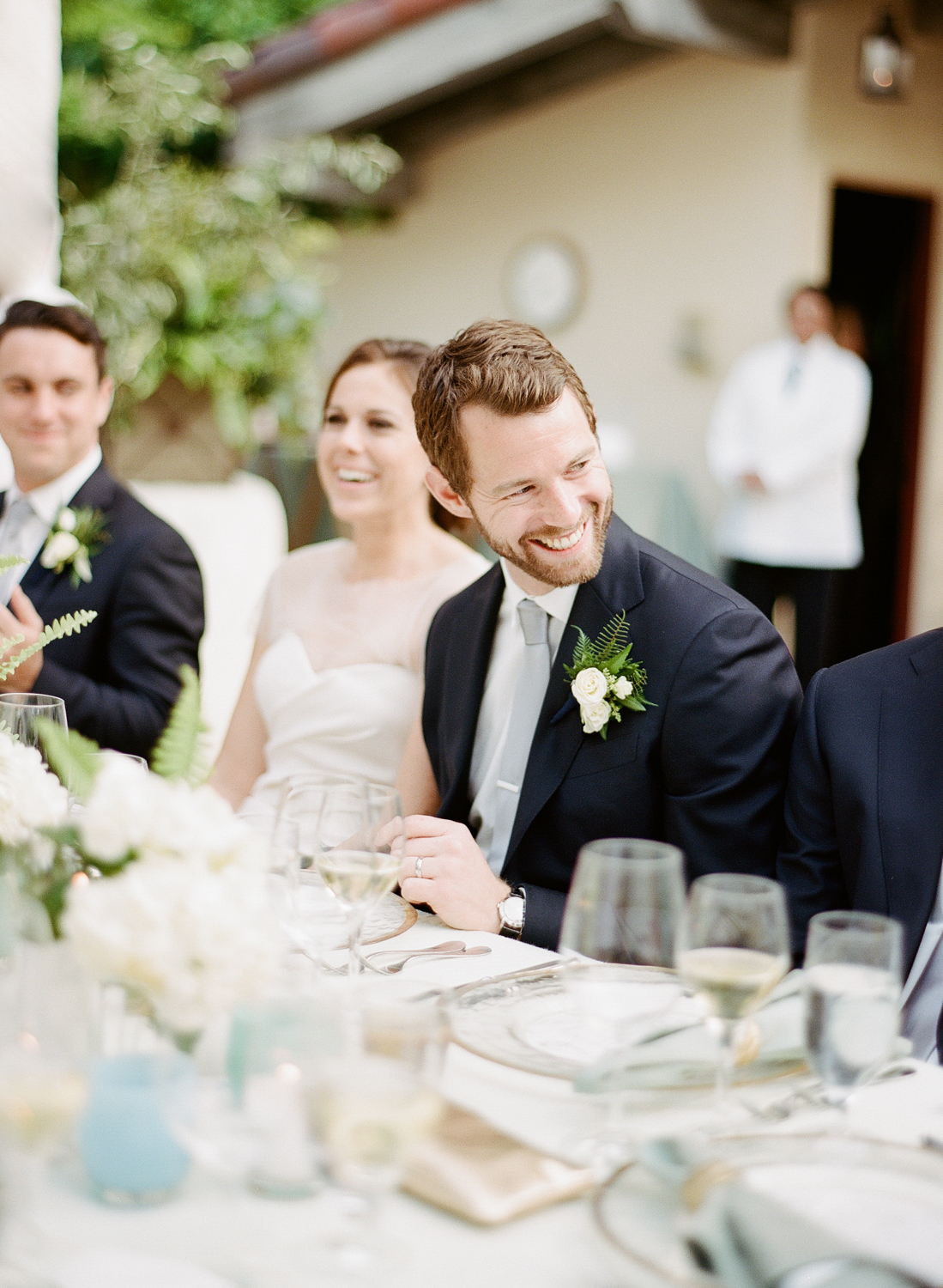 Bride and groom laugh during outdoor reception toasts; Sylvie Gil Photography