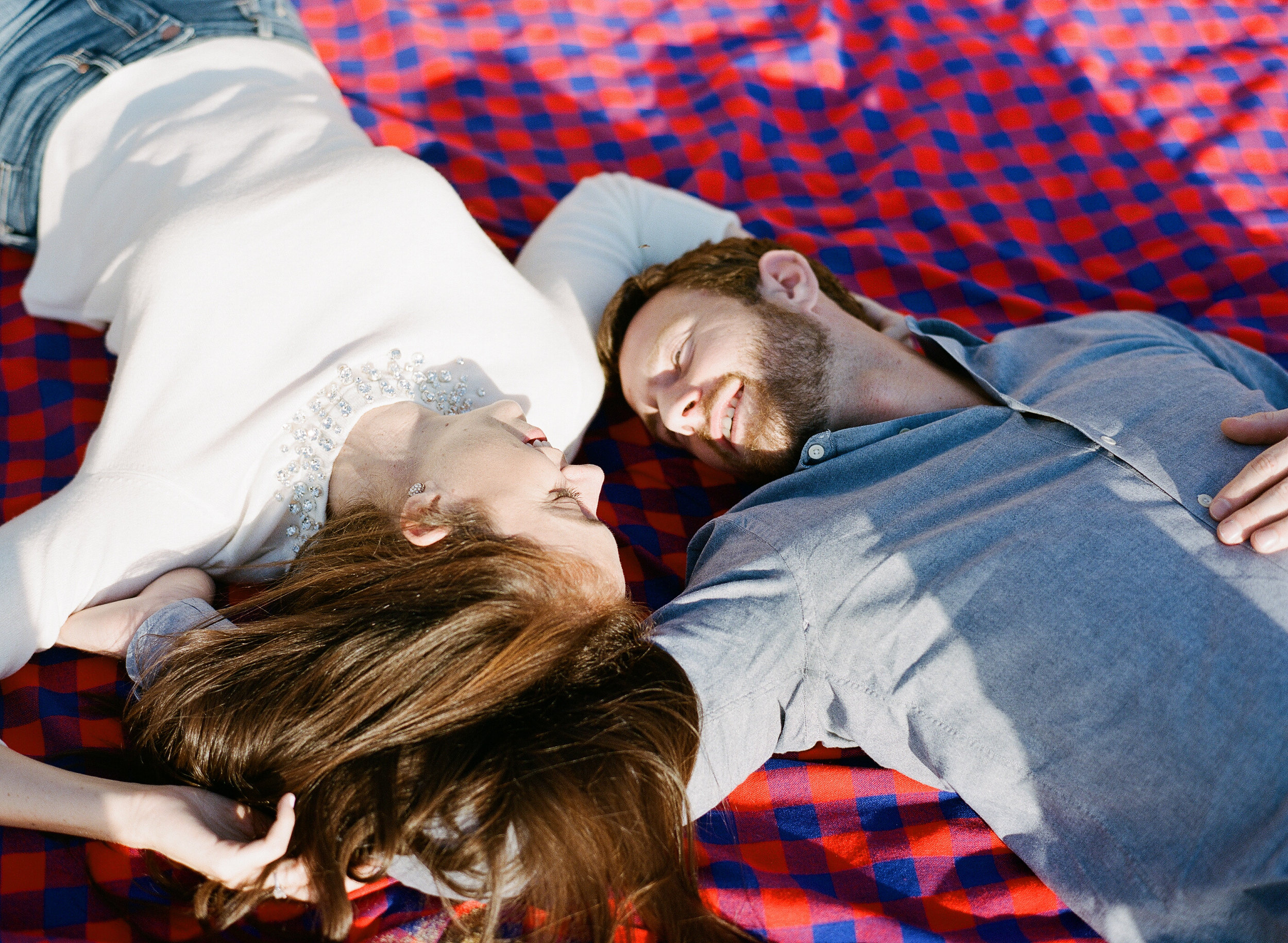 Couple on a beach blanket during engagement photo shoot; Sylvie Gil Photography