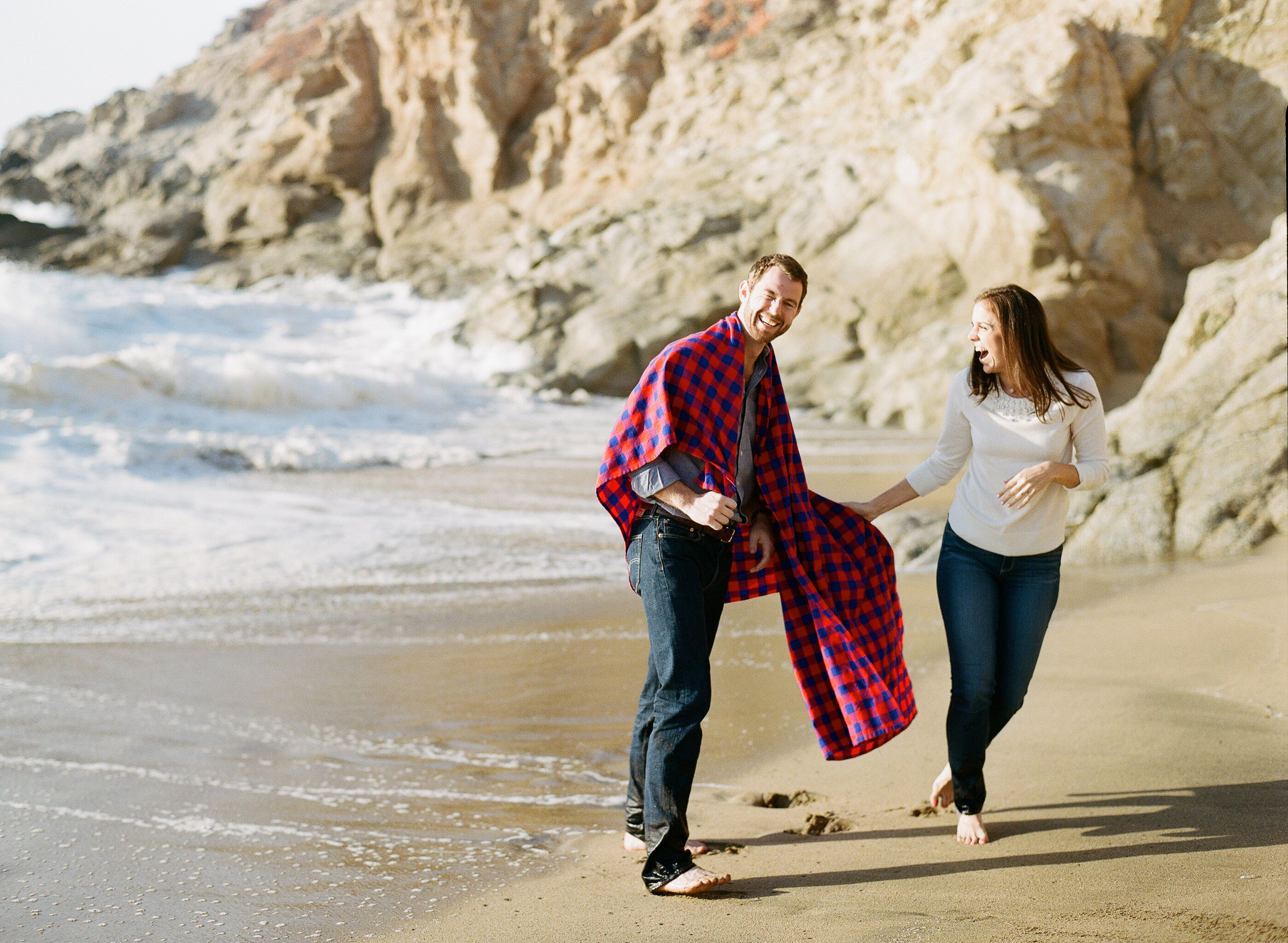 Couple plays on the beach during engagement session photo shoot; Sylvie Gil Photography
