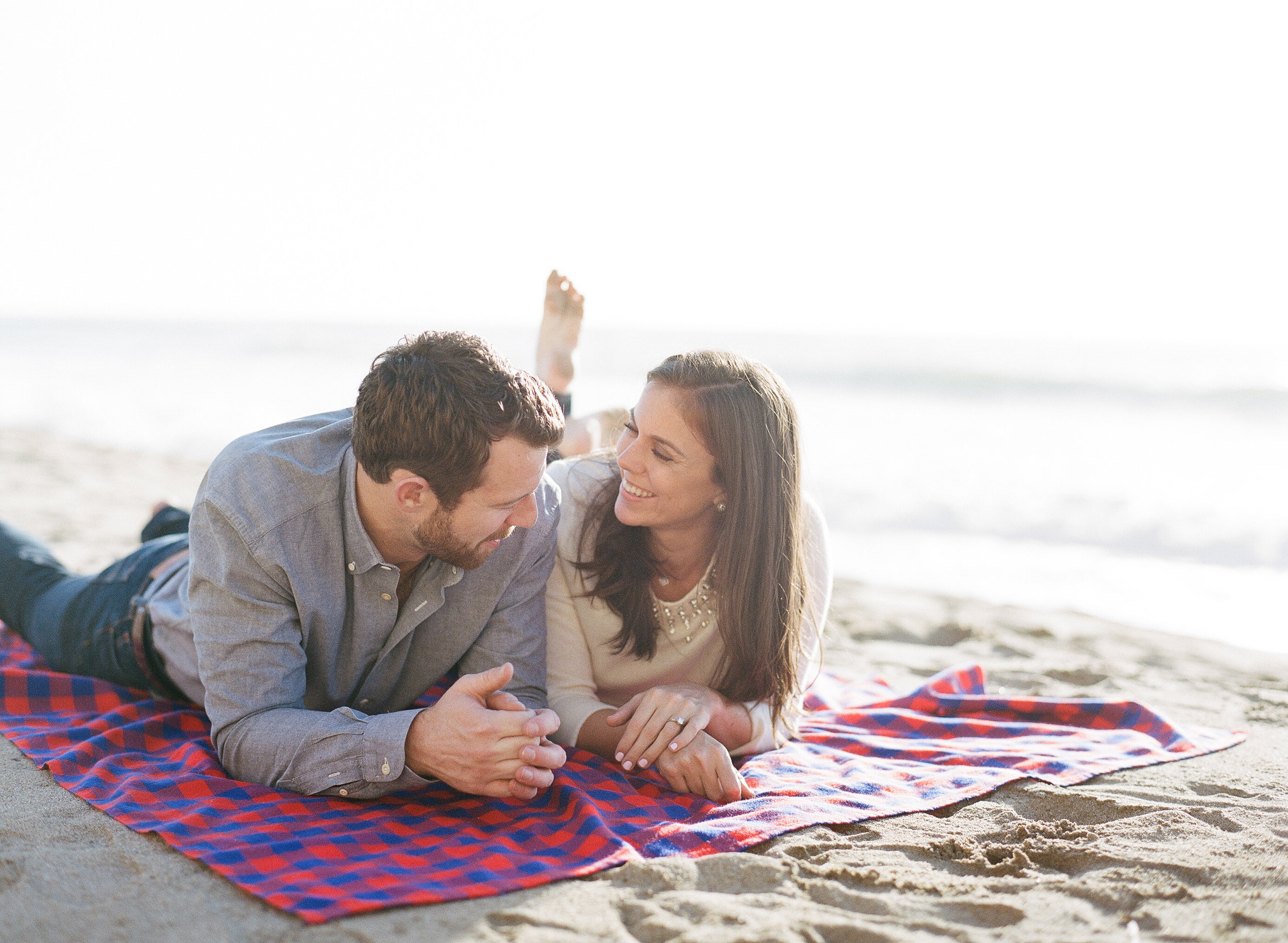 Couple on beach blanket during engagement session; Sylvie Gil Photography