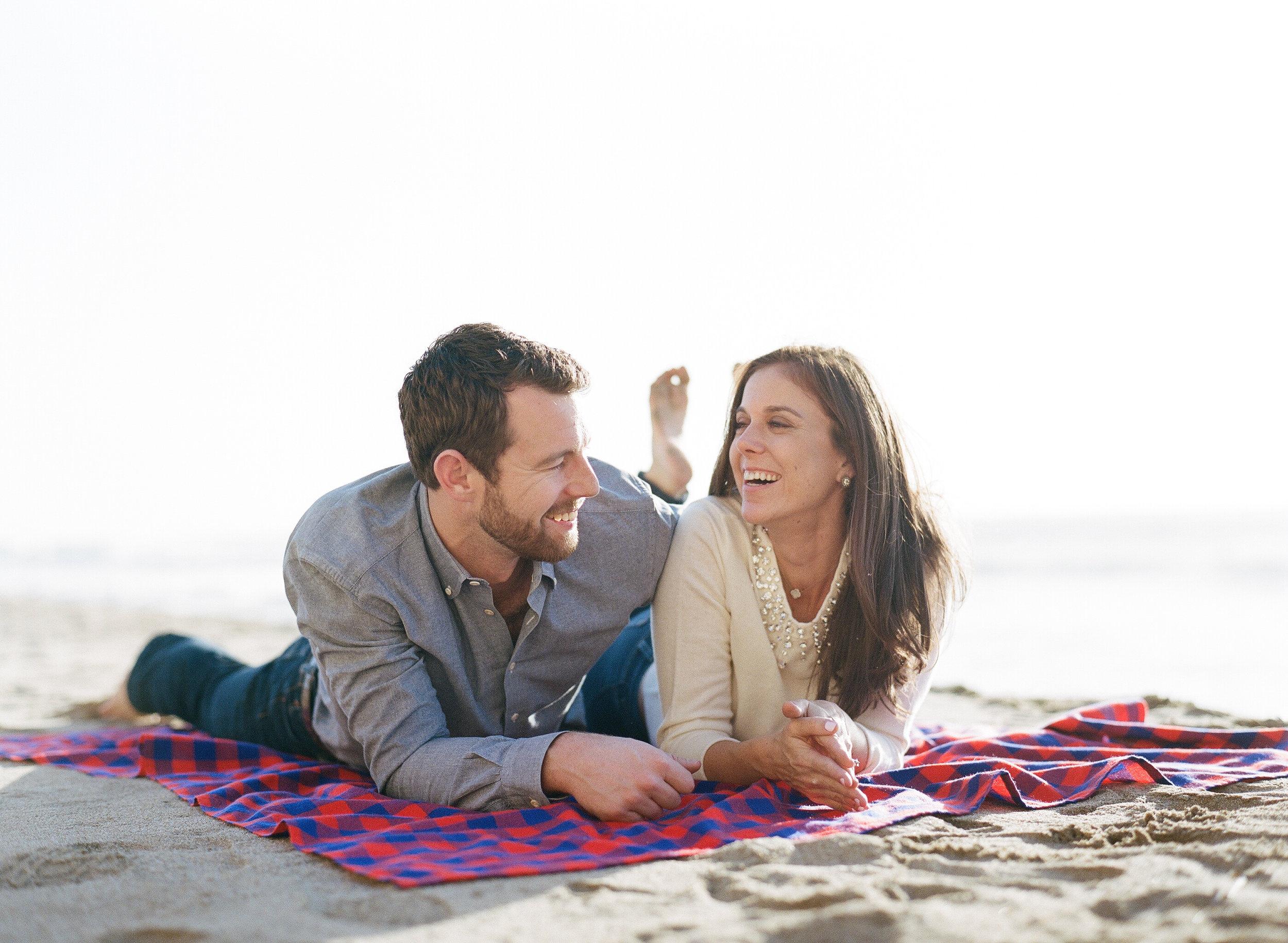 Couple laughing on beach blanket, Northern California beach; Sylvie Gil Photography