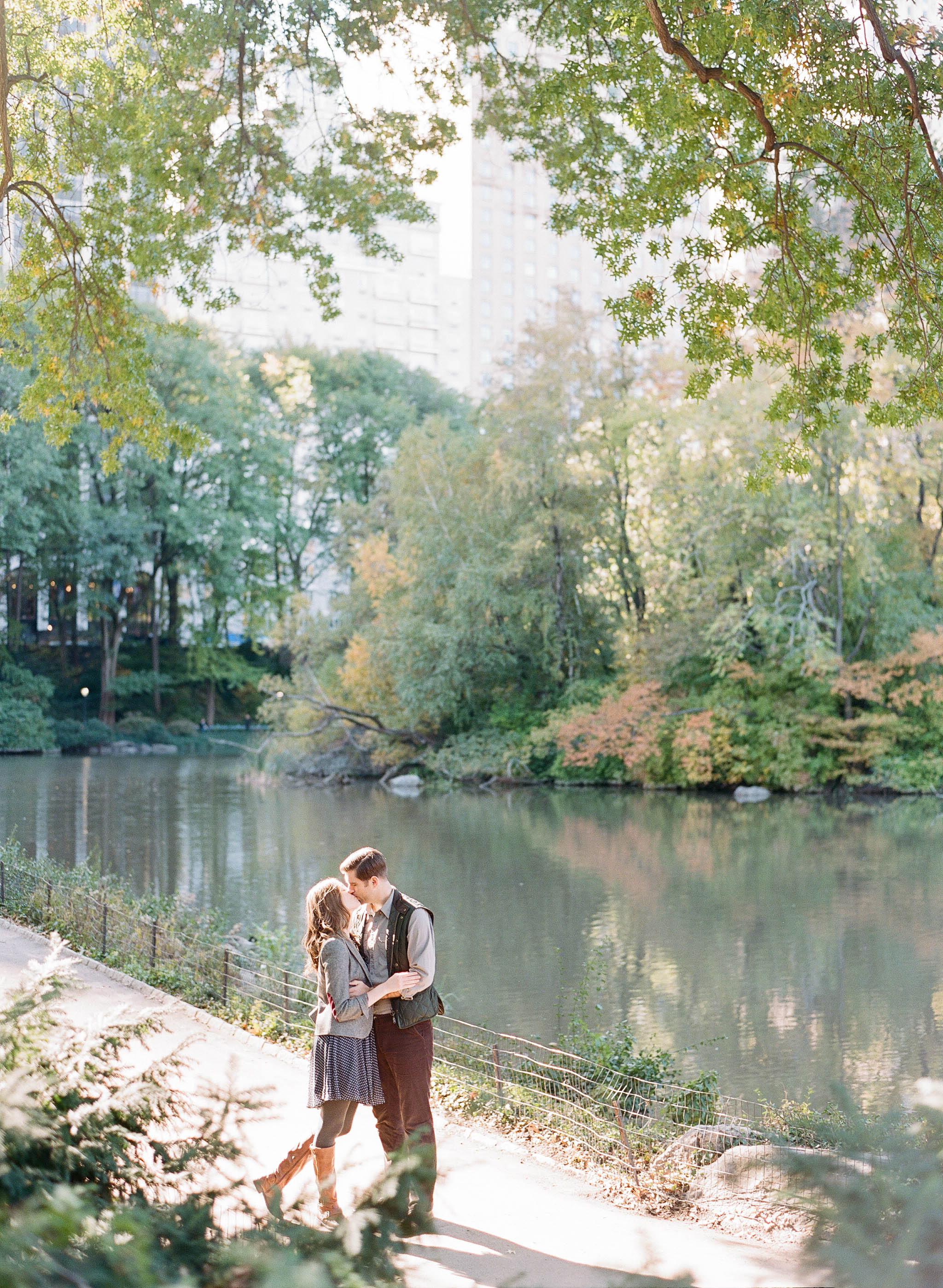 Couple kisses during autumn engagement session next to pond in Central Park, New York City; Sylvie Gil Photography