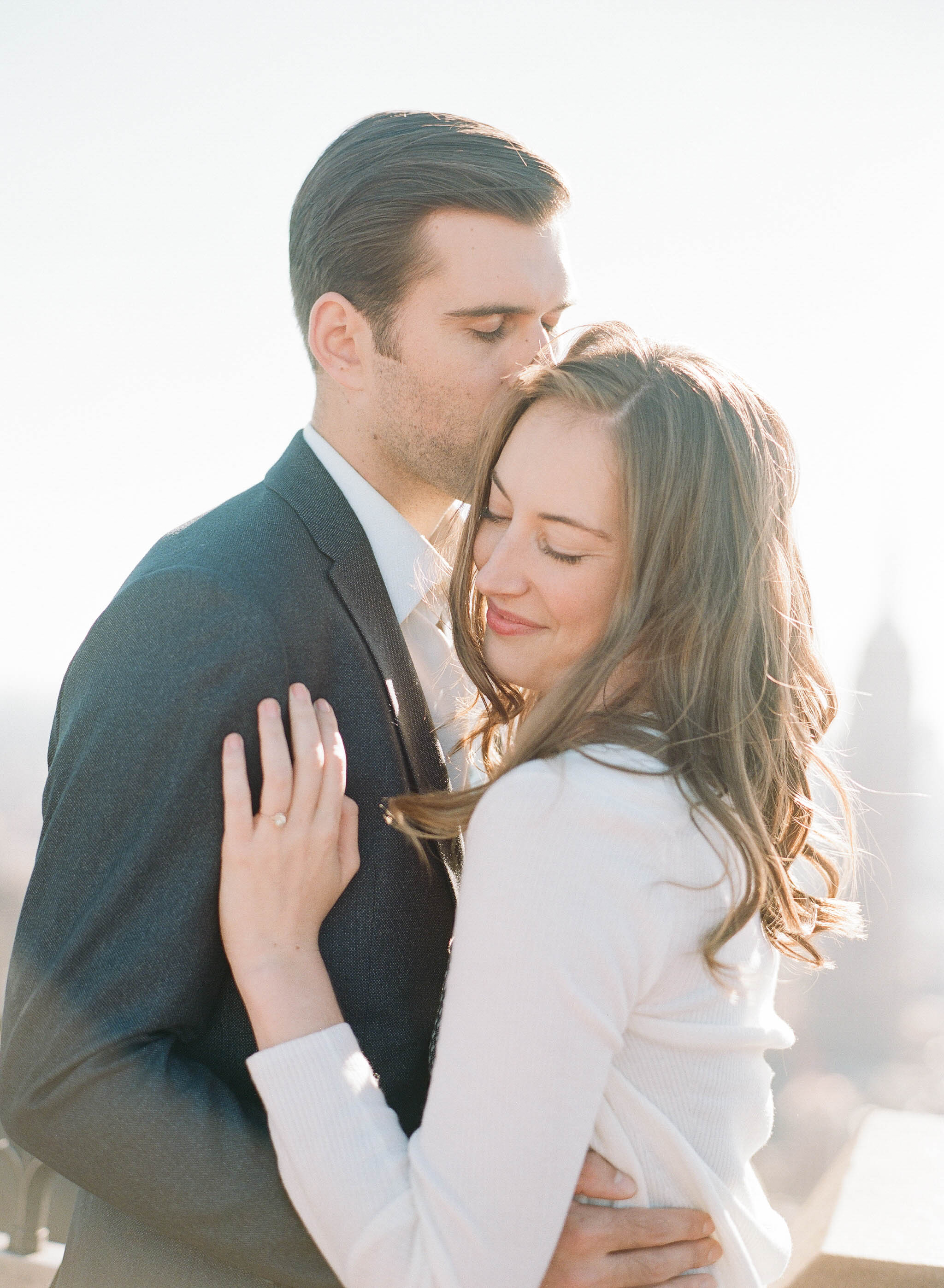 Future groom kisses his future bride at sunset in New York City during an engagement photoshoot; Sylvie Gil Photography