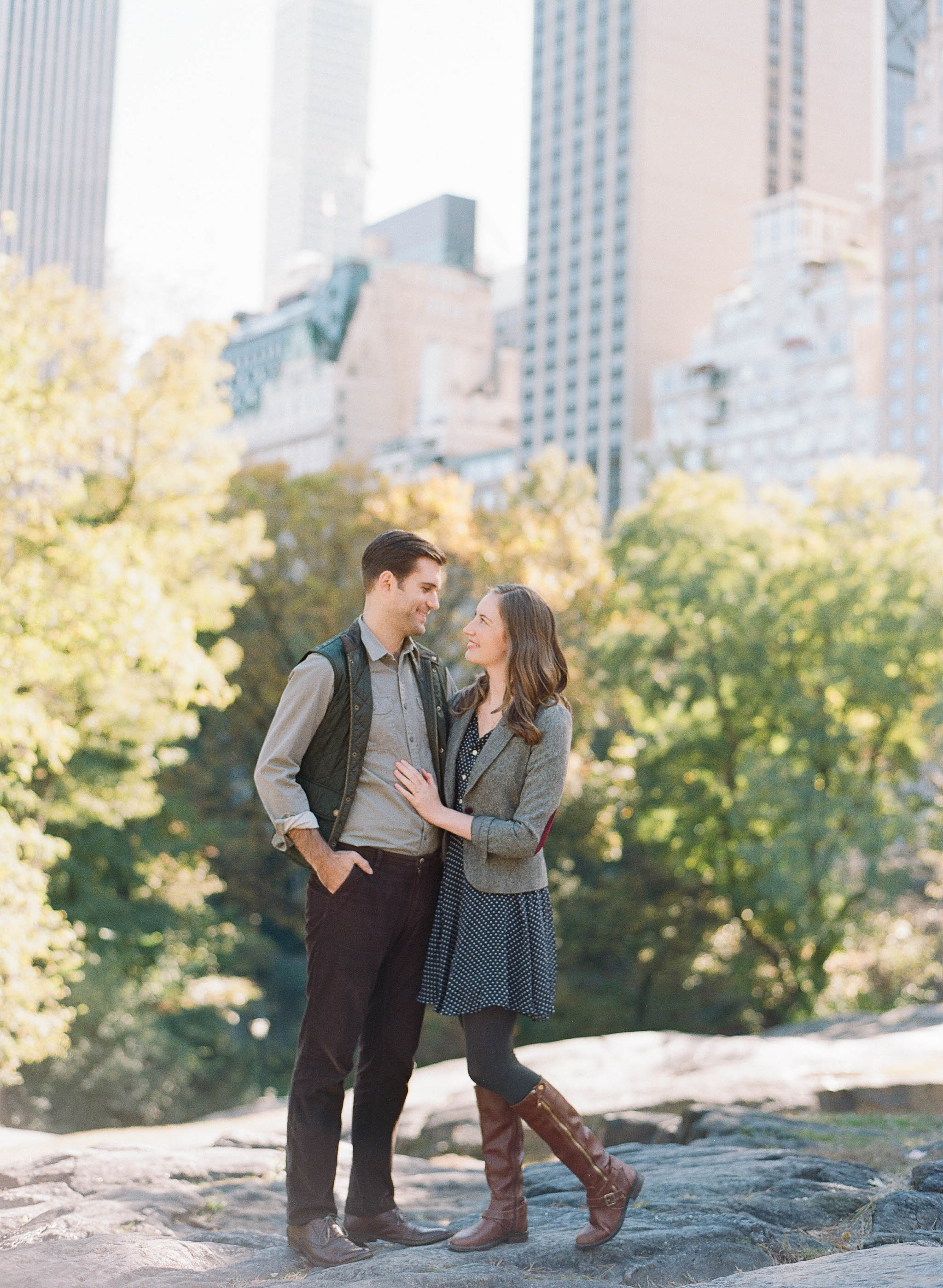 Couple stands on a boulder in Central Park, New York City for an engagement session; Sylvie Gil Photography