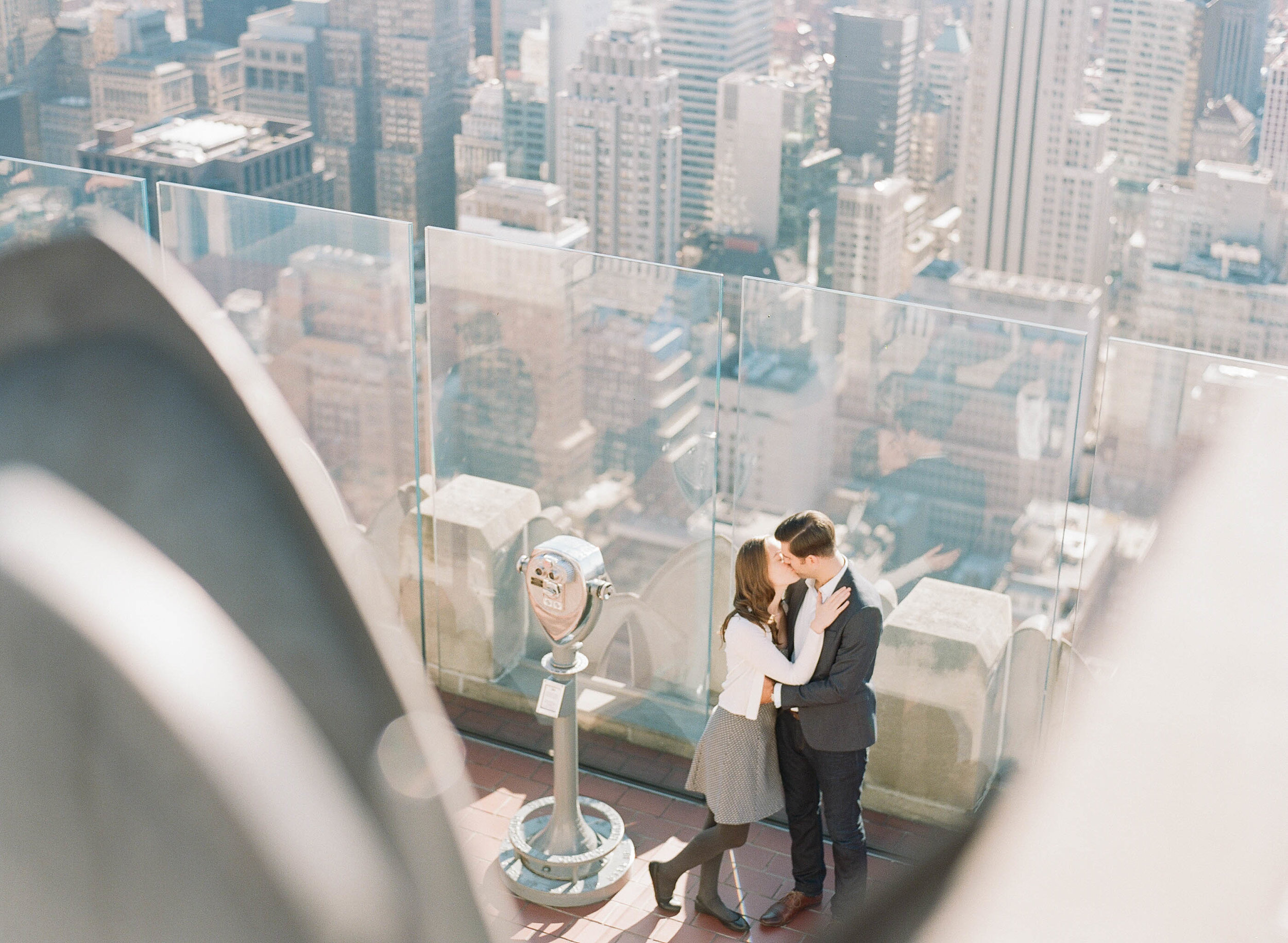 Couple kisses on the roof of a skyscraper during an autumn engagement session in New York City; Sylvie Gil Photography