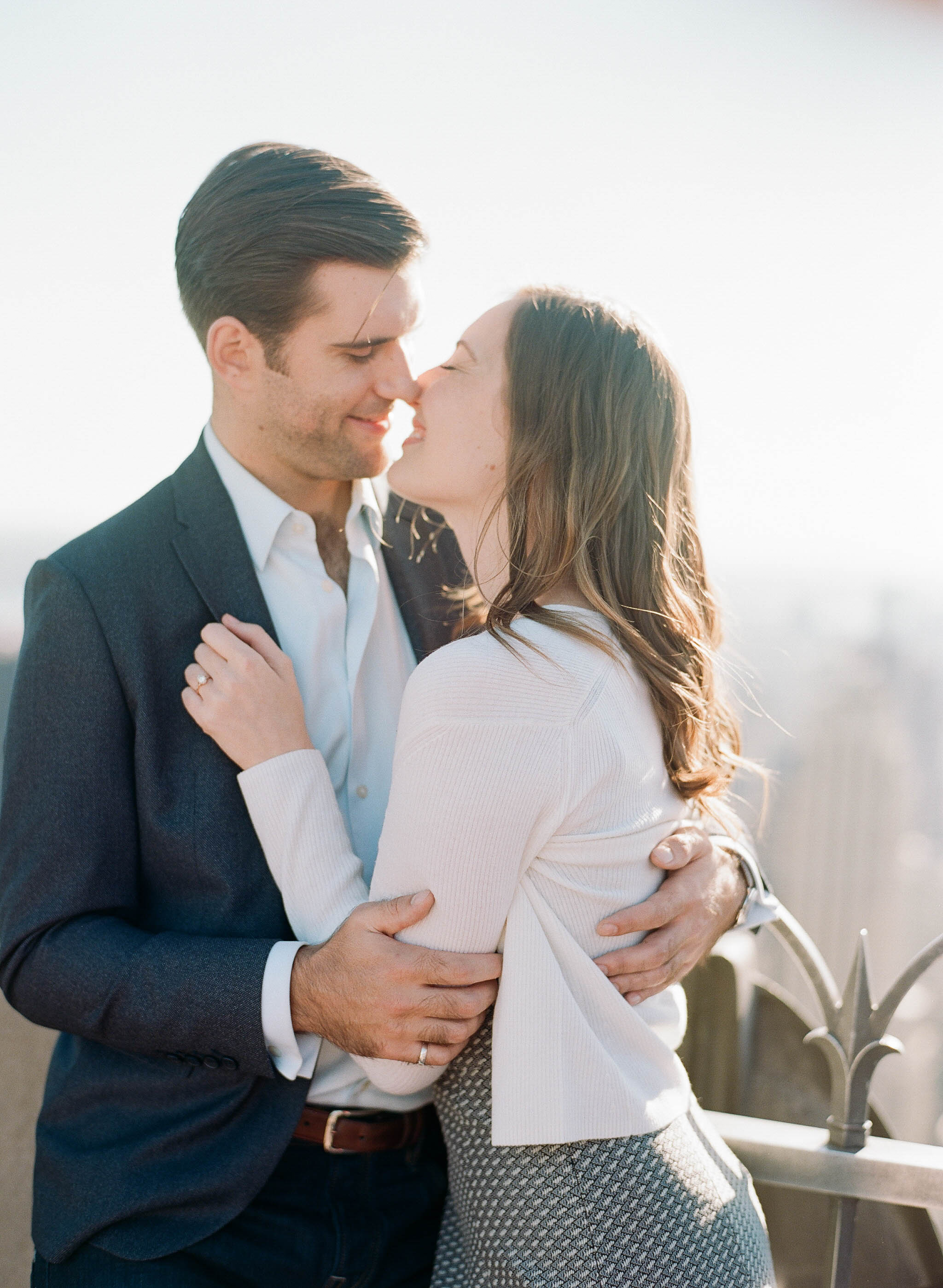 Couple about to kiss during a late summer engagement session on the roof of a midtown New York City skyscraper; Sylvie Gil Photography