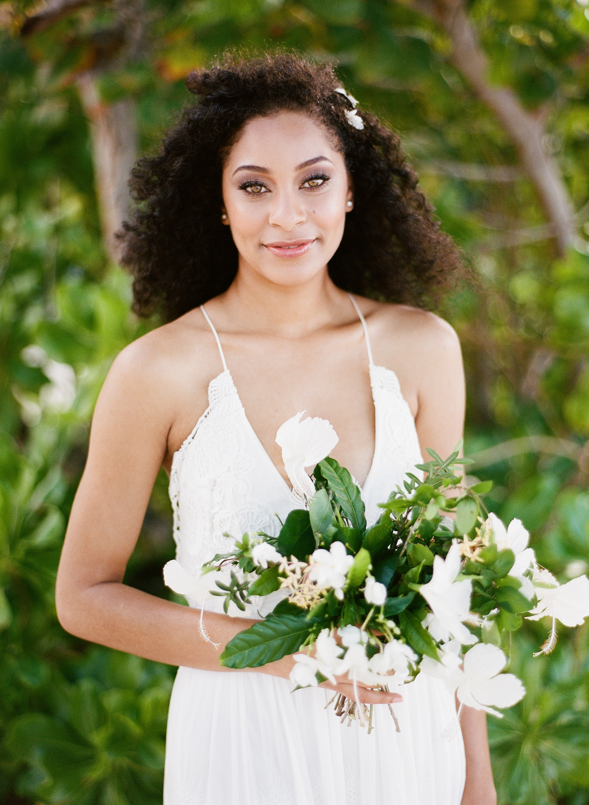 Tropical Caribbean bride in flowy gown and with hibiscus bouquet; Sylvie Gil Photography