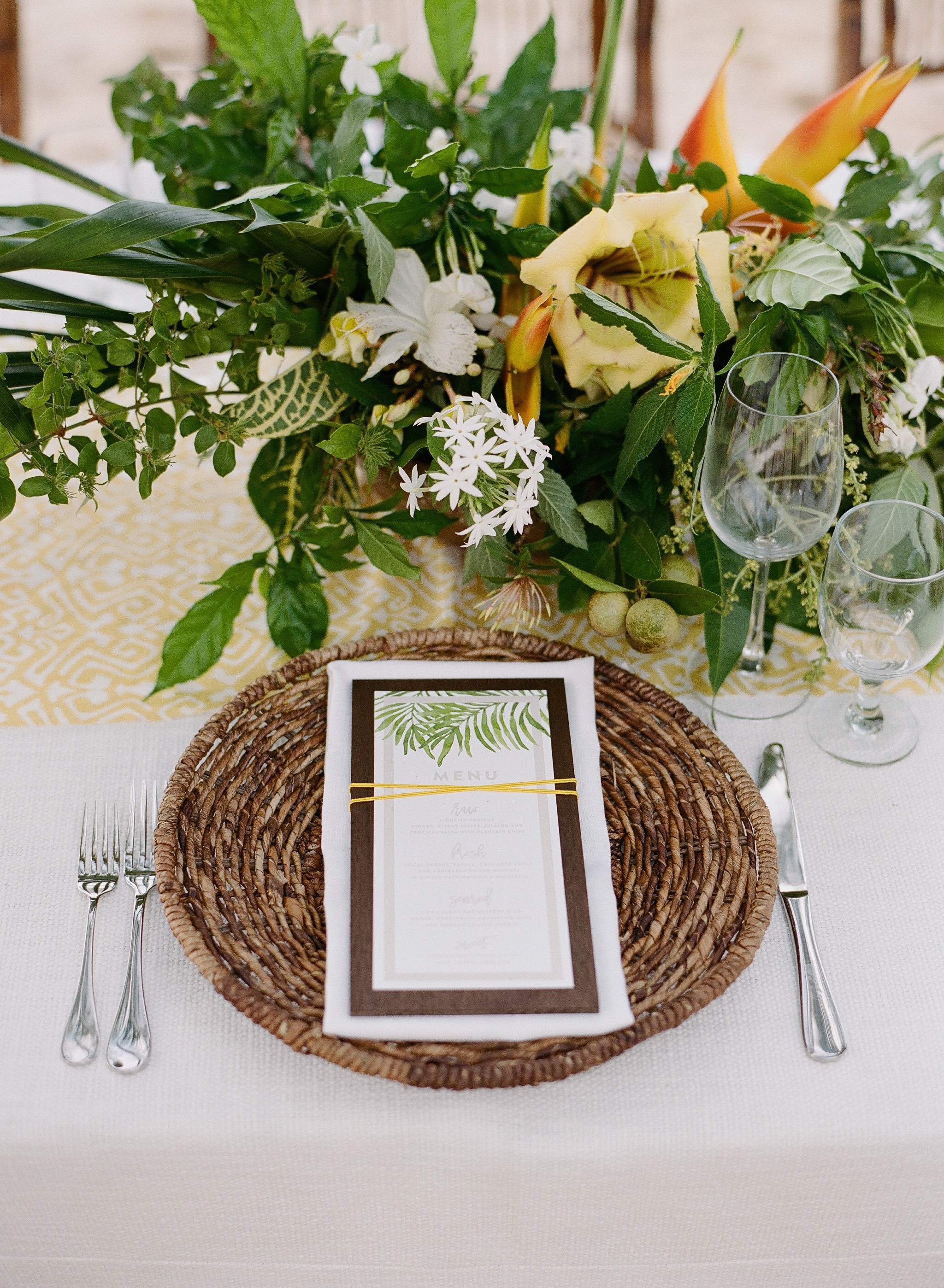 Wicker place setting, tropical bloom centerpiece and menu card at beach reception table in Montego Bay, Jamaica; Sylvie Gil Photography