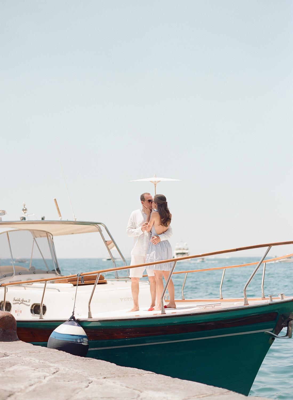 Newlyweds kiss on the deck of a yacht off the Amalfi Coast; Sylvie Gil Photography