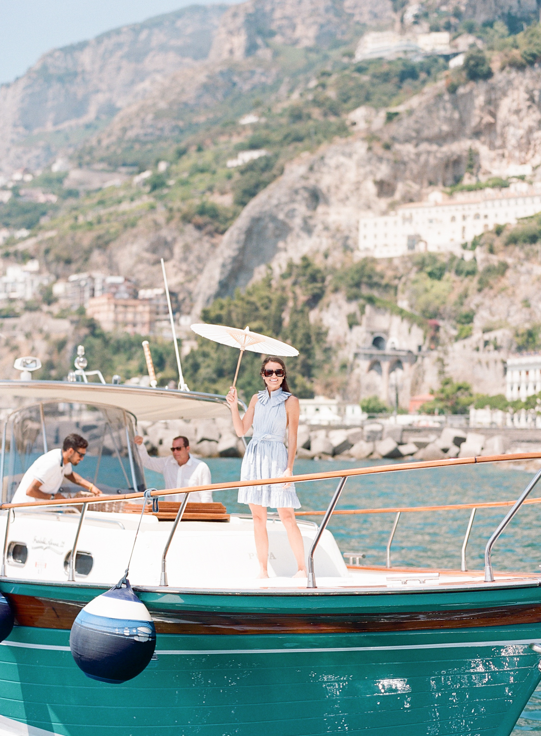Bride stands on the deck of a yacht with a parasol; Sylvie Gil Photography
