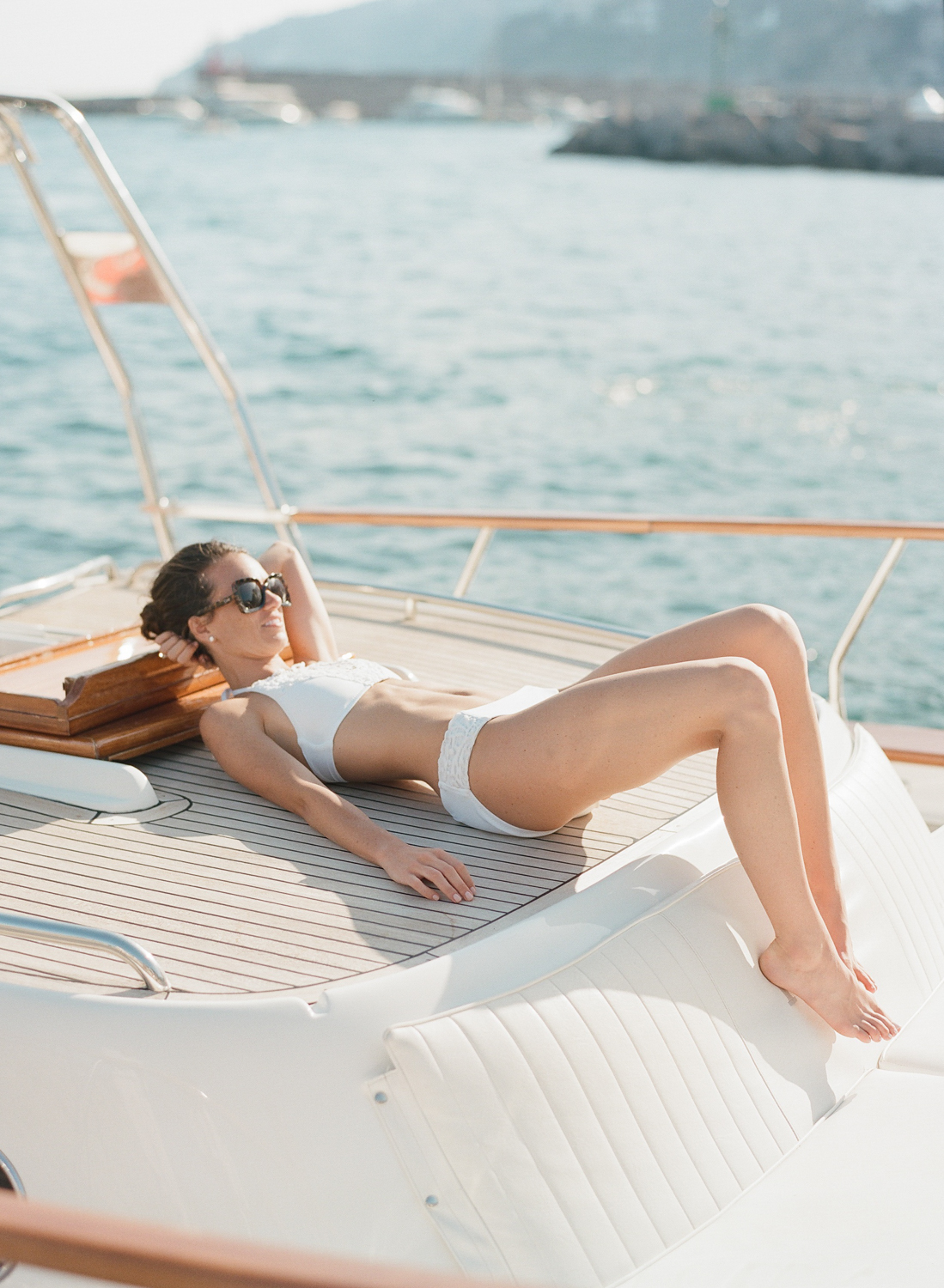 Bride lies on the deck of a yacht, docked outside a beach club in Positano on the Amalfi Coast; Sylvie Gil Photography