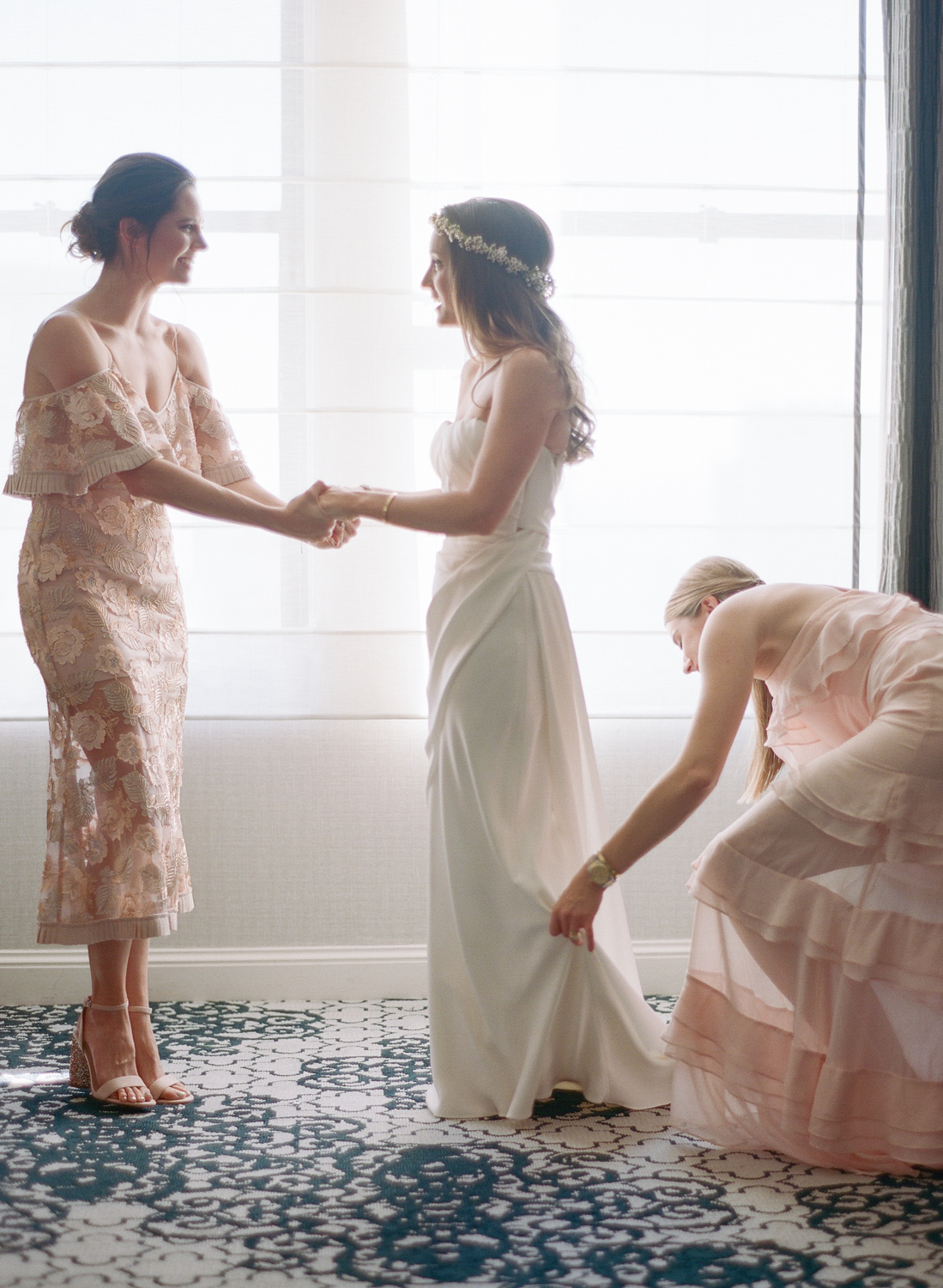 Bridesmaids help the bride into her dress; Sylvie Gil Photography