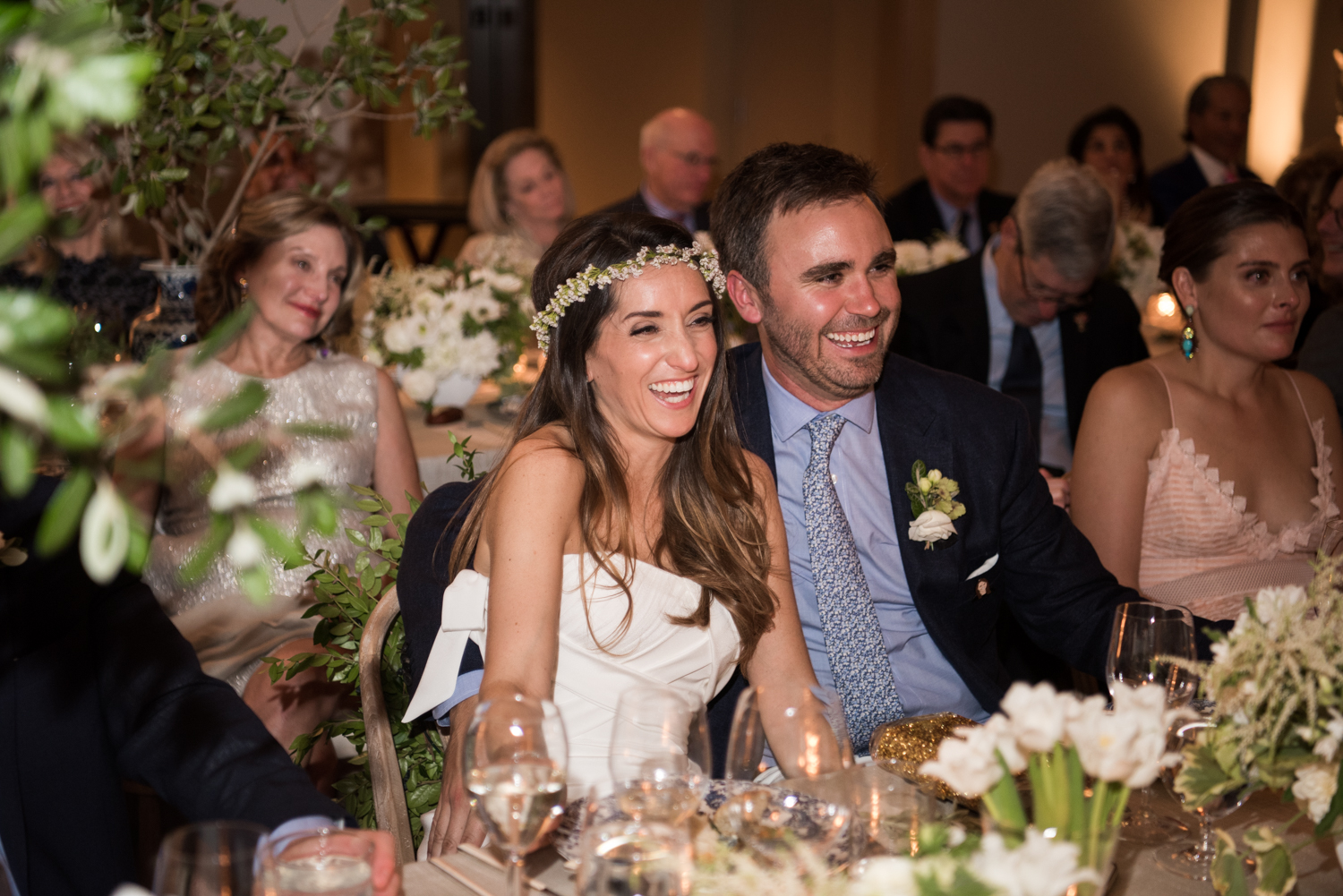 The bride and groom together at the wedding reception listening to toasts; Sylvie Gil Photography