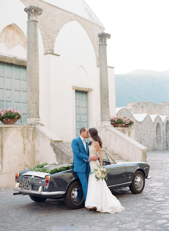 The couple kisses against a vintage car in Amalfi Coast, Italy; Sylvie Gil Photography
