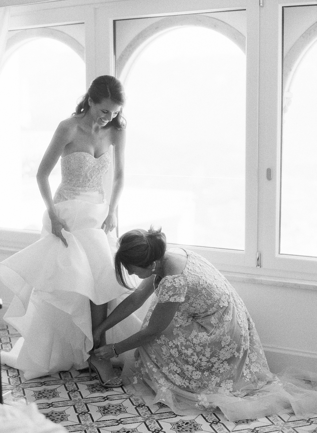 The bride's mother helps her put on her shoes before the wedding ceremony; Sylvie Gil Photography
