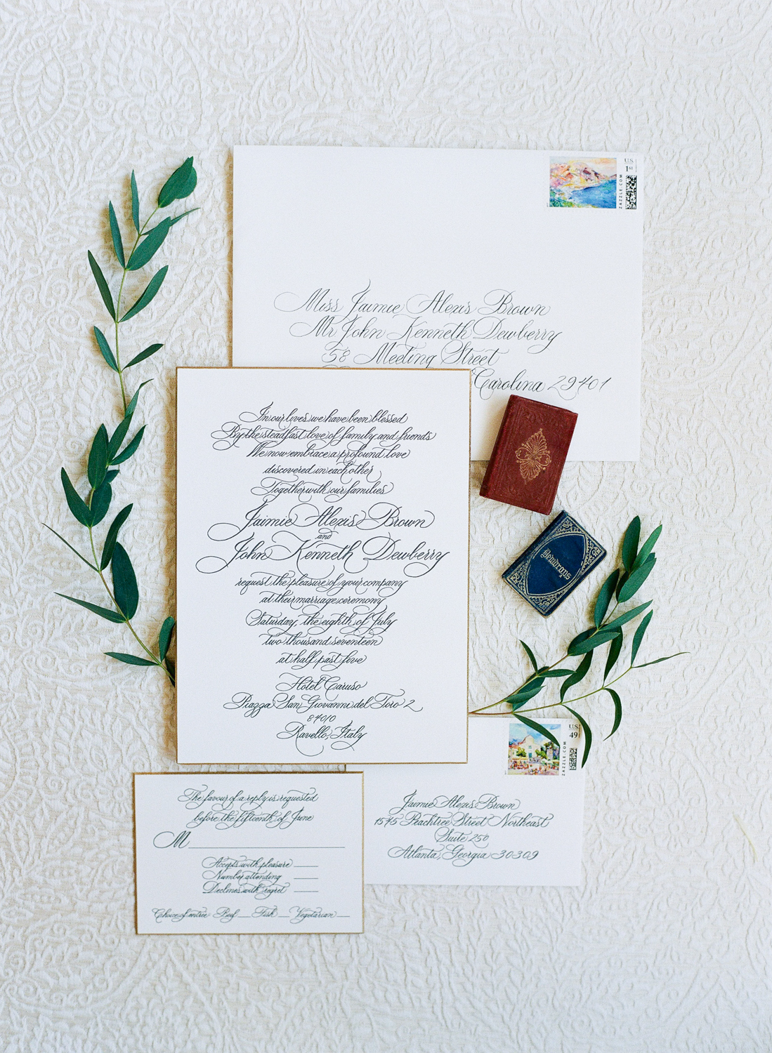 A layflat of the invitation, framed with olive branches; Sylvie Gil Photography
