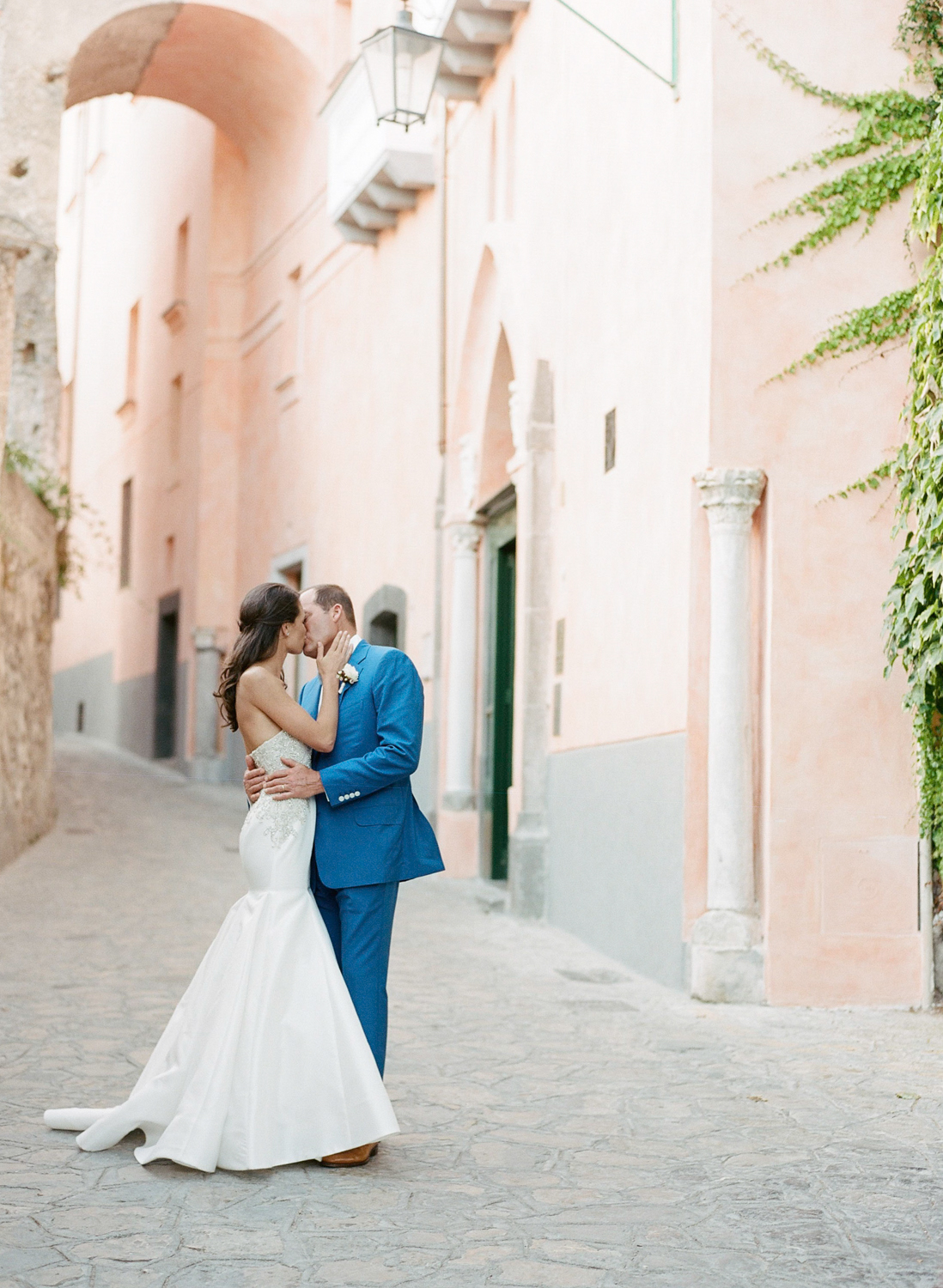 The bride and groom kiss on a street in Ravello, Italy on the Amalfi Coast; Sylvie Gil Photography