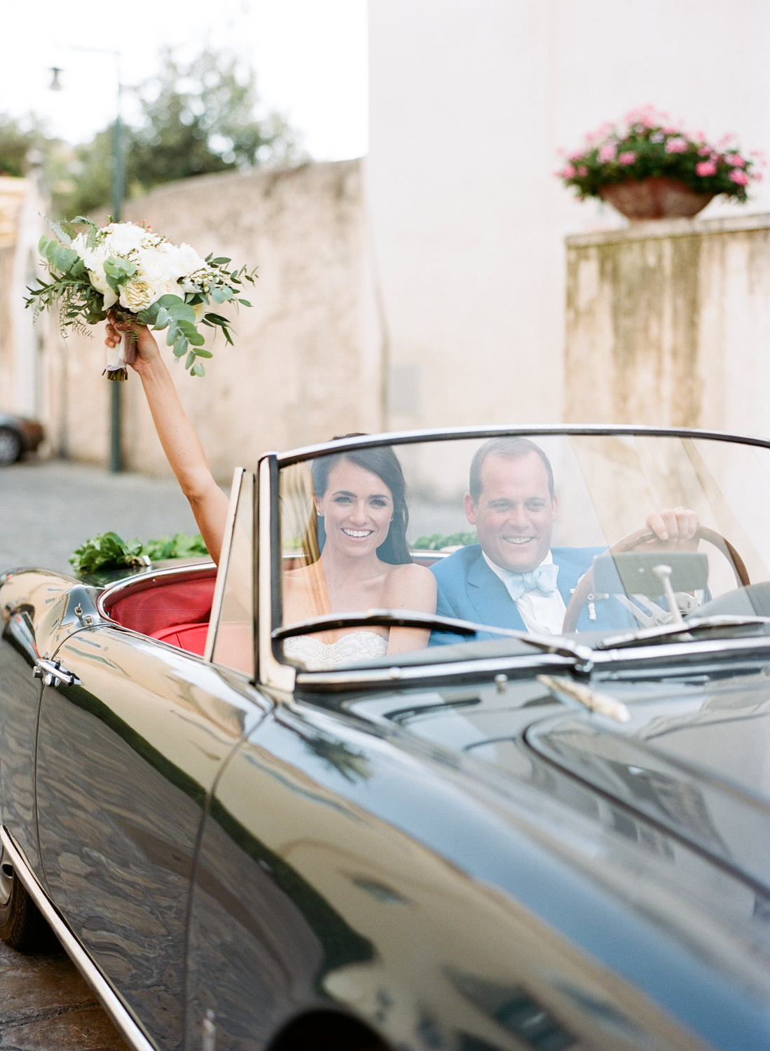 A portrait of the bride and groom in a vintage car after the wedding ceremony in Ravello, Italy; Sylvie Gil Photography