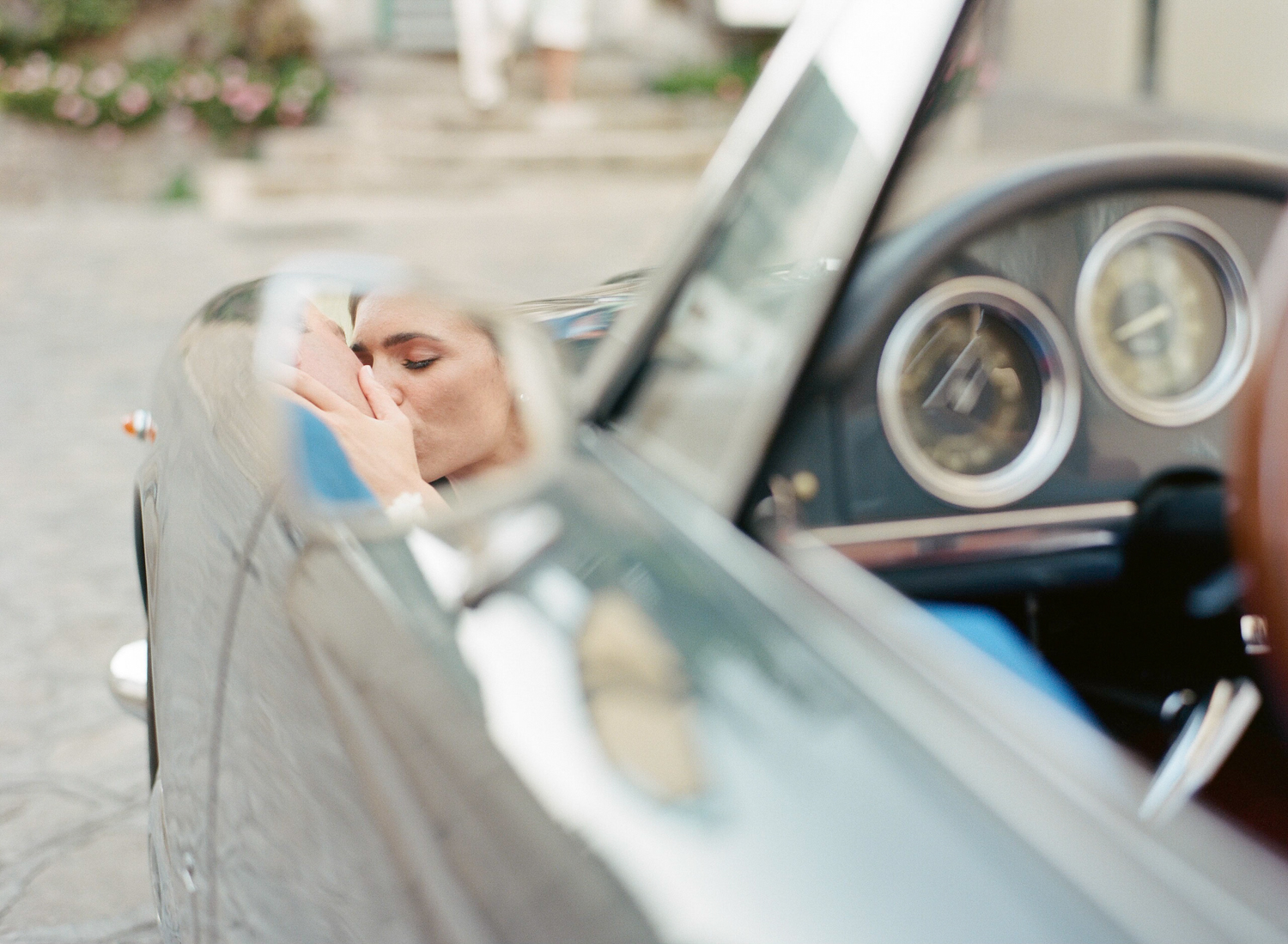 The bride kisses her groom in the rear view mirror of a vintage car; Sylvie Gil Photography