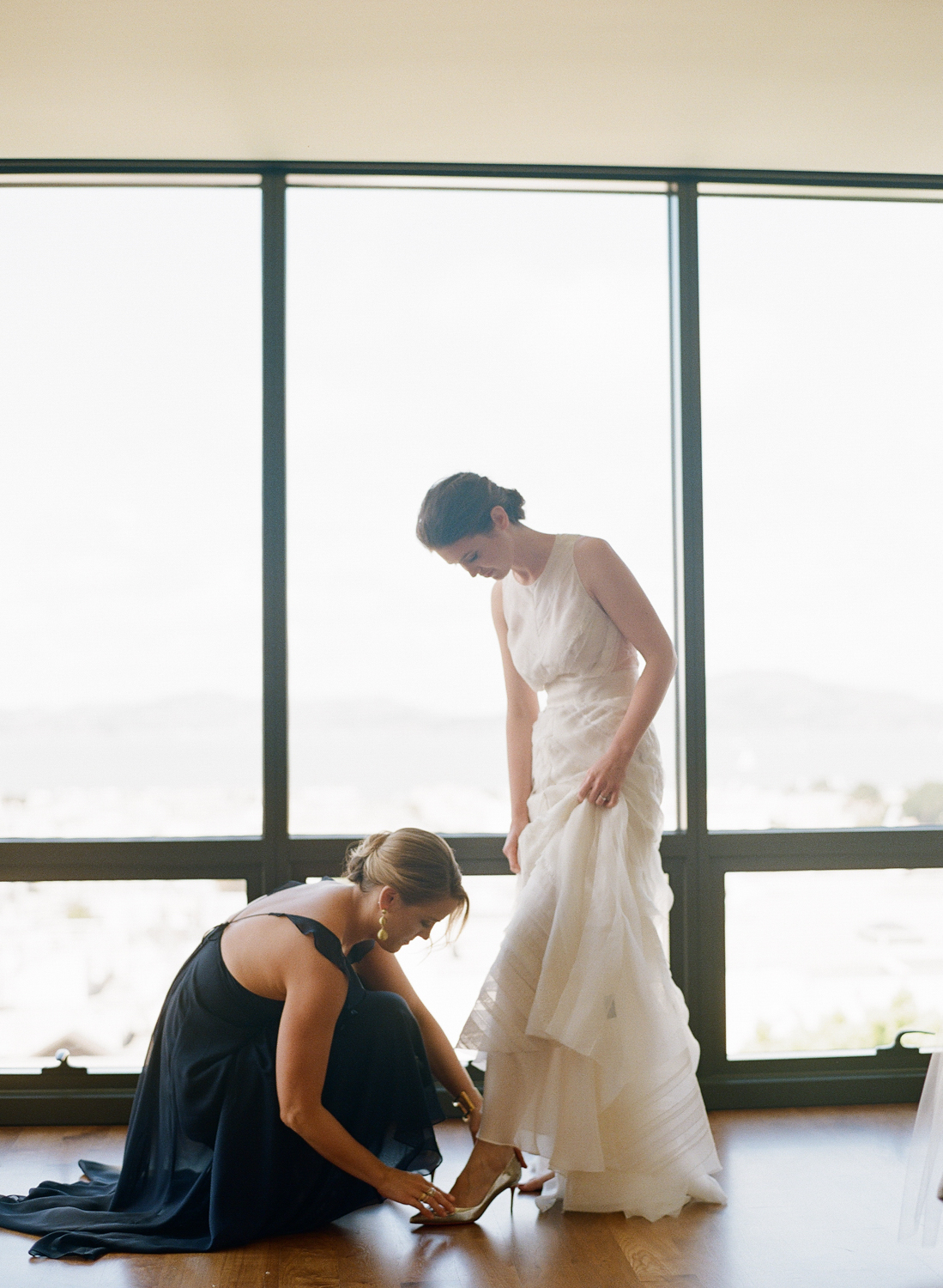The brides sister and maid of honor helps her put on her shoes on her wedding day; Sylvie Gil Photography