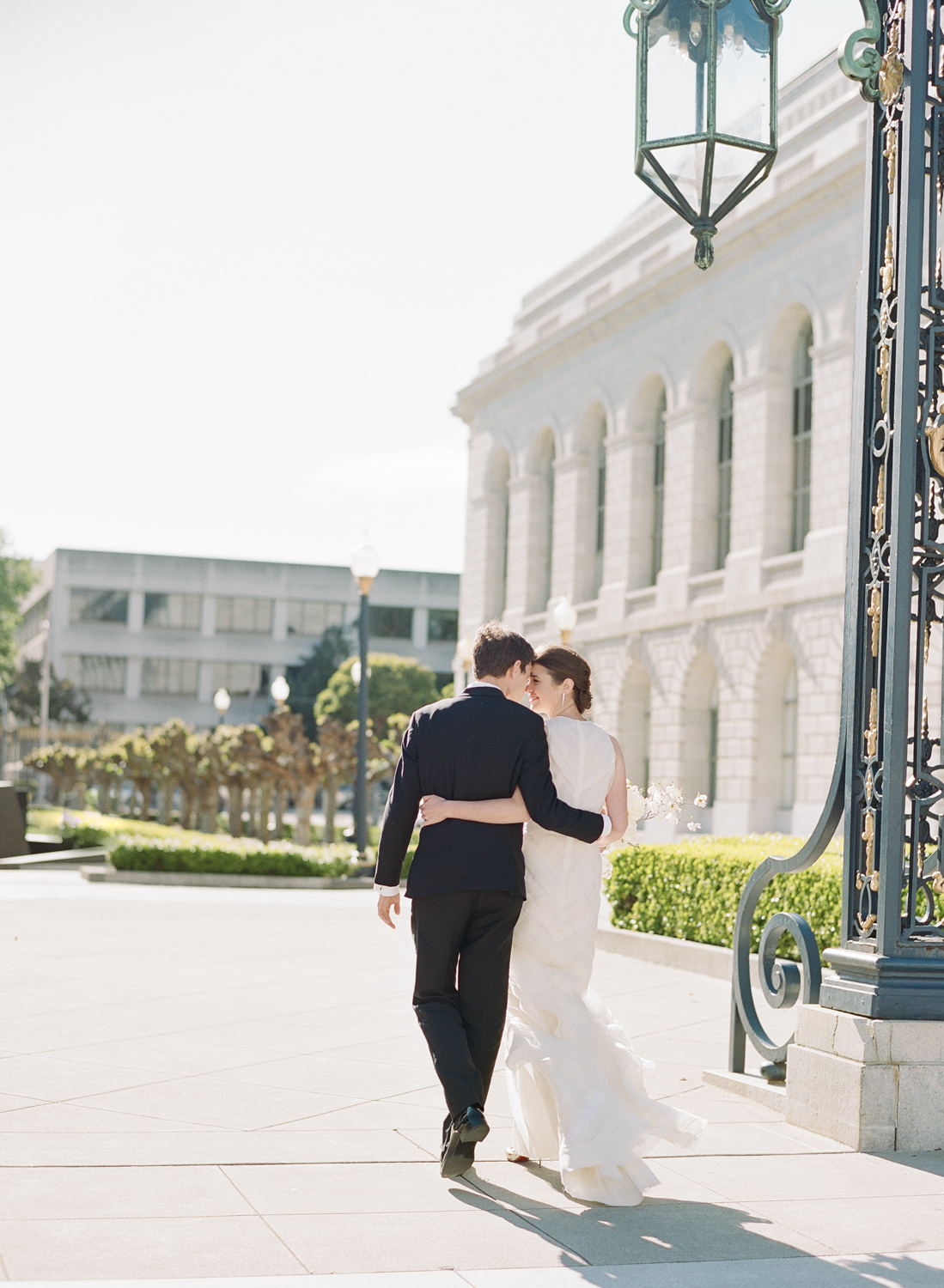 The bride and groom walk through the gate at San Francisco City Hall before the wedding; Sylvie Gil Photography