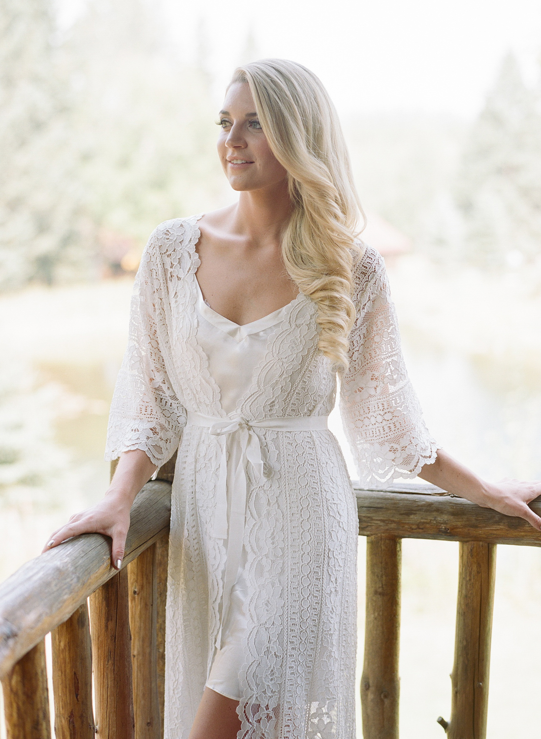 Kaitlin, the bride, stands in a lace robe before the wedding in Whitefish, Montana; Sylvie Gil Photography