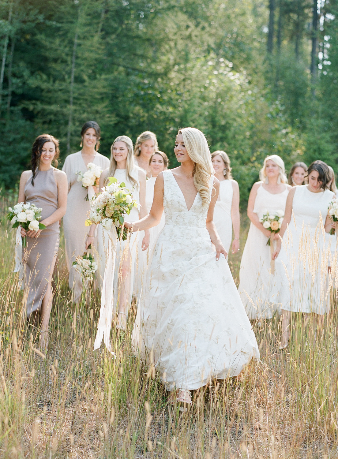 Bride and bridesmaids walk through a meadow near Whitefish, Montana before the wedding ceremony; Sylvie Gil Photography