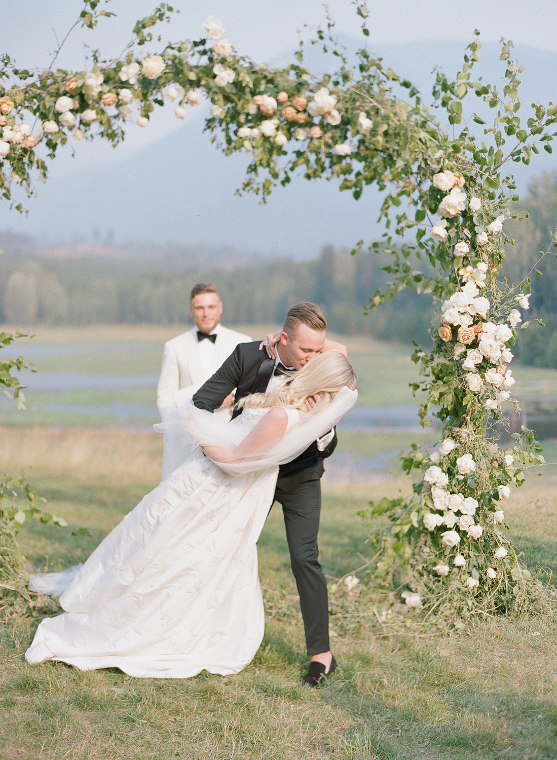 The groom dips the bride for the first kiss at the ceremony in Whitefish, Montana; Sylvie Gil Photography