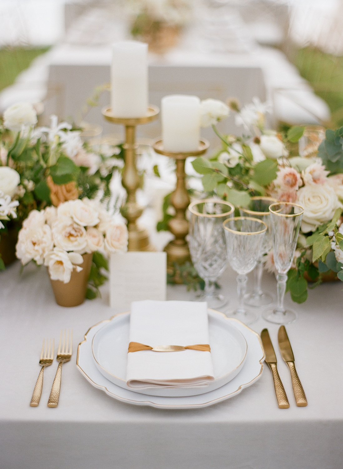 A gold-accented table setting at a wedding reception in Whitefish, Montana; Sylvie Gil Photography